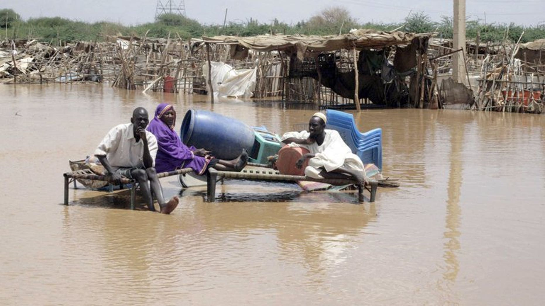 Men sit with their belongings on a flooded Khartoum street last week. Heavy rains and flash floods in Khartoum and other parts of Sudan have killed 11 people and affected almost 100,000 in the past week, the United Nations said on Tuesday.