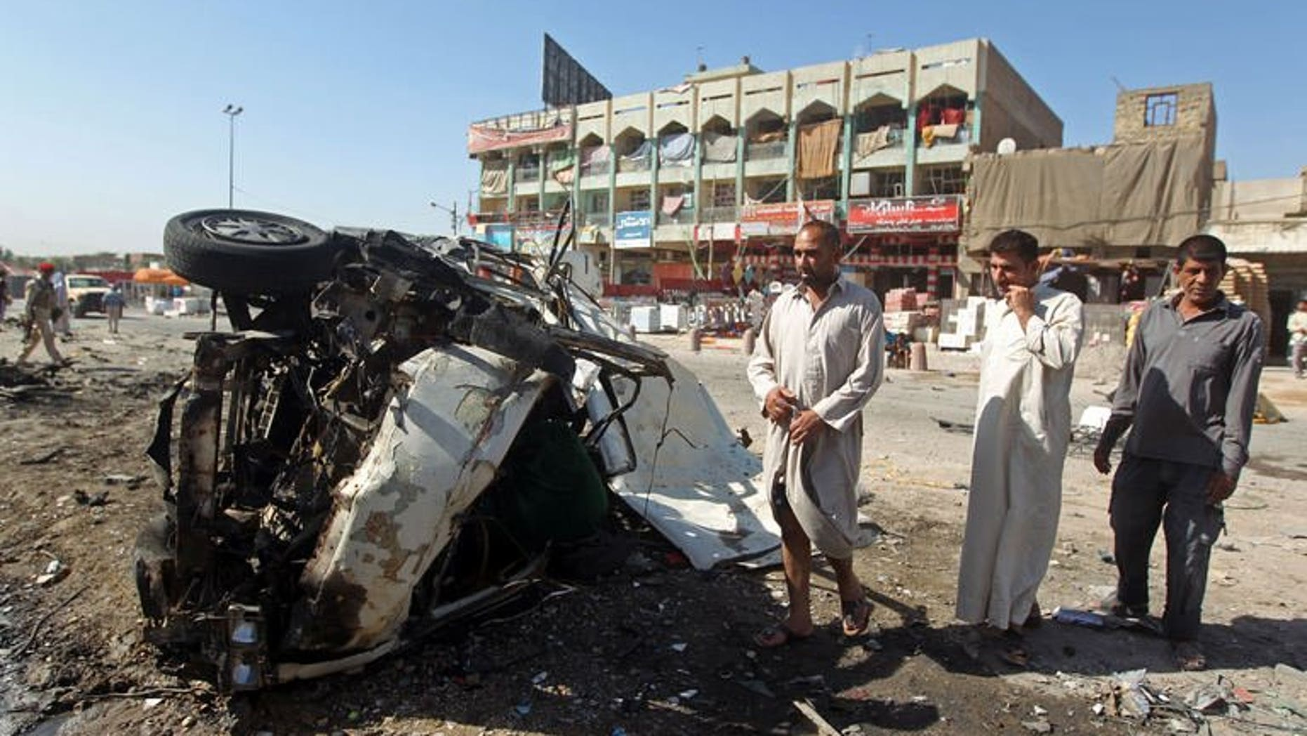July 29, 2013 shows Iraqis inspecting the site of a car bomb explosion in the impoverished district of Sadr City in Baghdad. A series of apparently coordinated bombings struck Baghdad on Tuesday, killing 12 people, while five others died in violence elsewhere in Iraq, officials said.