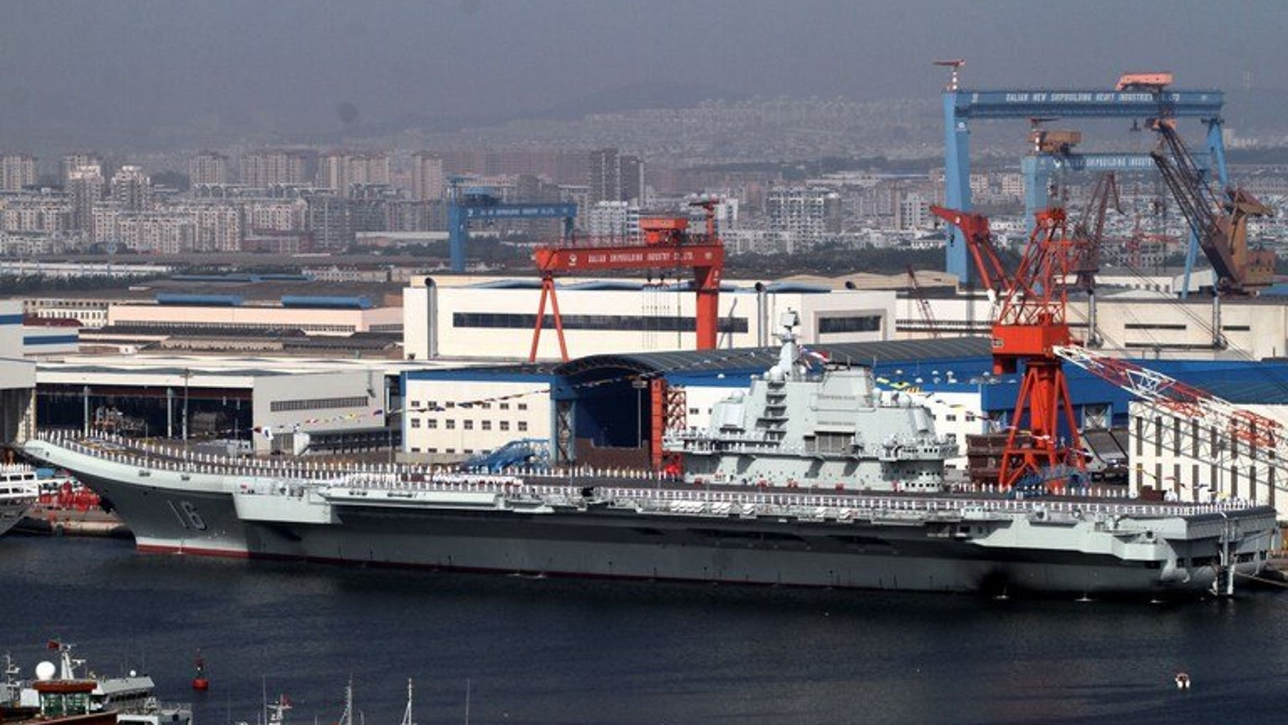 """China's first aircraft carrier, the """"Liaoning"""" sits berthed at the naval base in Dalian, northeast China's Liaoning province on September 25, 2012. No-one can contain China's rise, a leading Beijing foreign policy thinker said Tuesday, warning Manila and Tokyo that they had been mistakenly emboldened by Washington in territorial disputes with his country."""