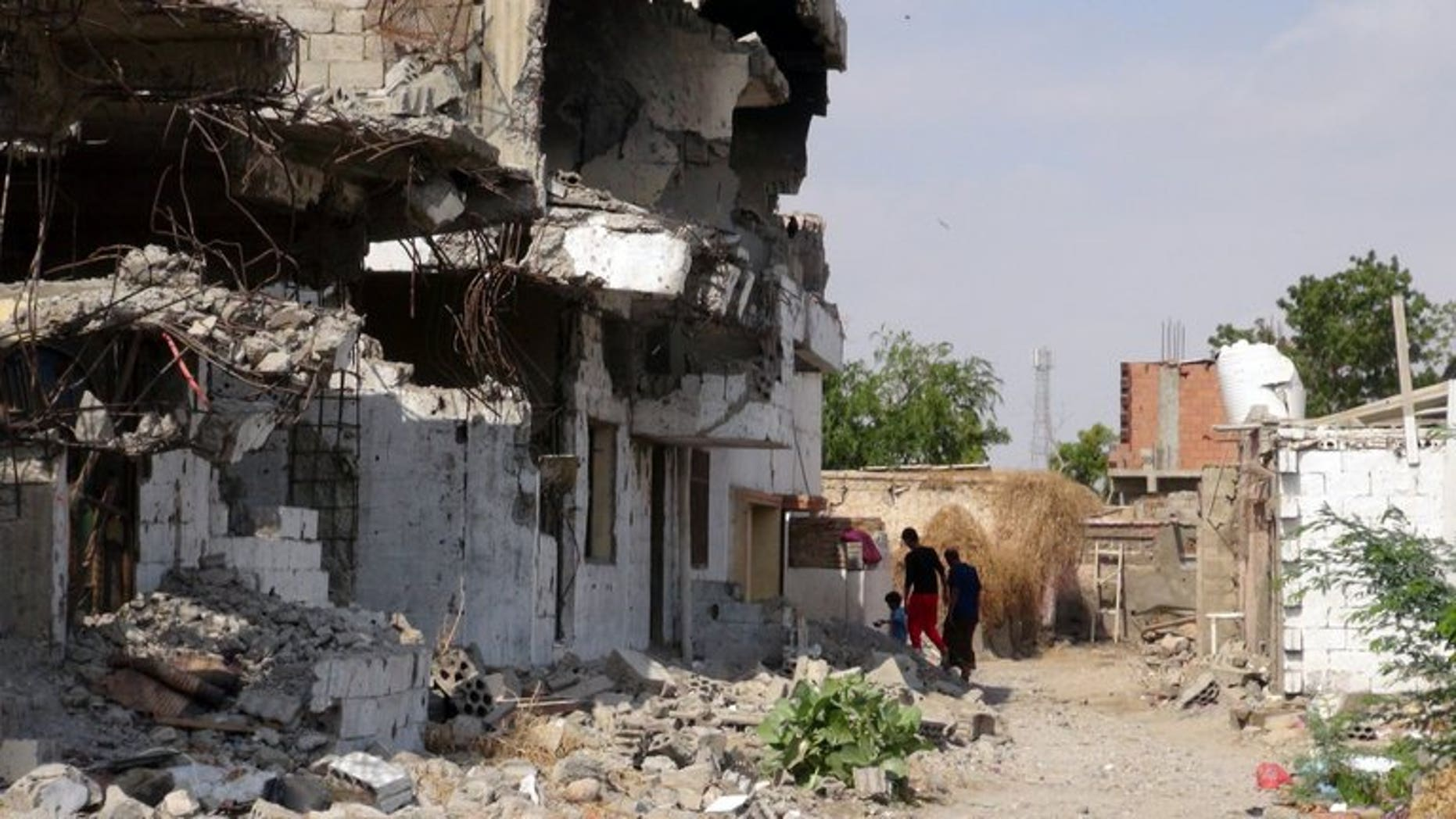 Yemenis walk past destroyed buildings in Zinjibar on December 5, 2012. Nasir al-Wuhayshi, a former aide to Al-Qaeda's late founder Osama bin Laden, tunnelled his way out of prison to become head of the Yemen-based Al-Qaeda in the Arabian Peninsula.