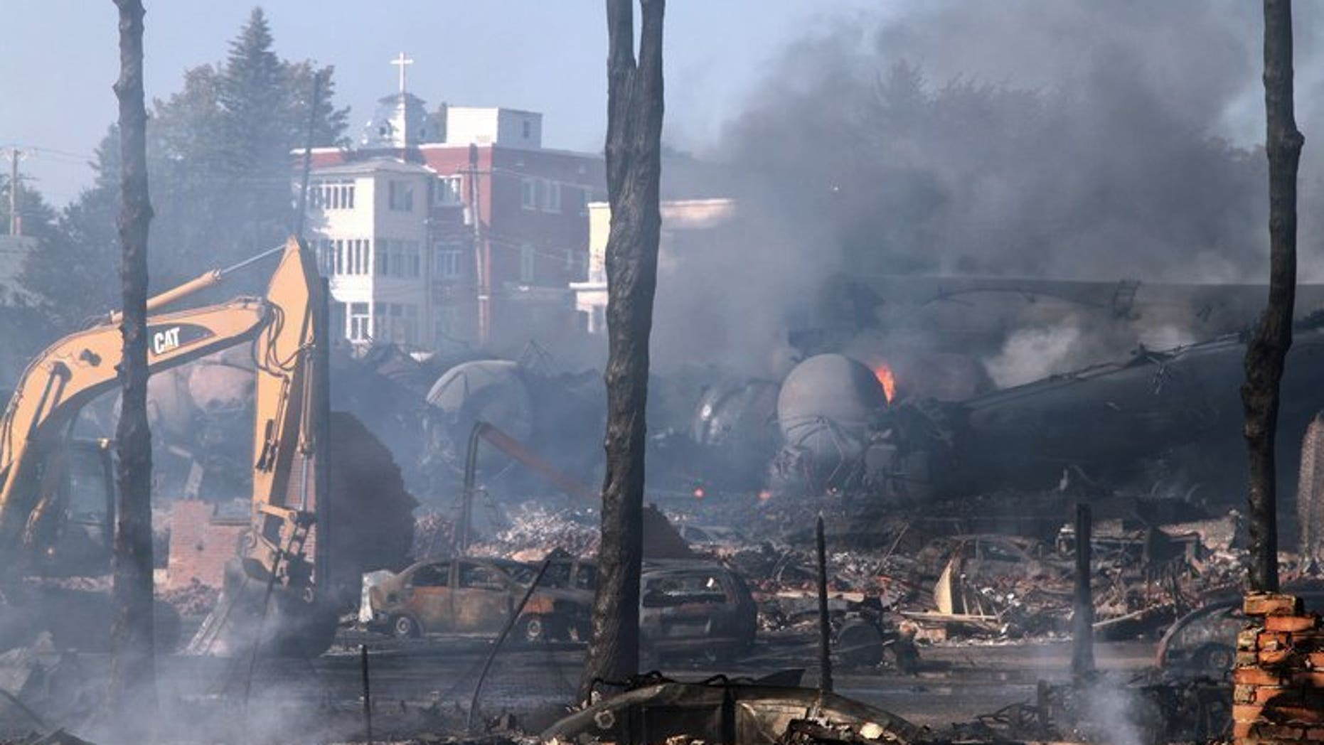 Wrecked oil tankers and debris are shown July 8, 2013 after a runaway train derailed and exploded in Lac-Megantic, Quebec. Montreal, Maine & Atlantic , the owners of the train, have filed for bankruptcy.