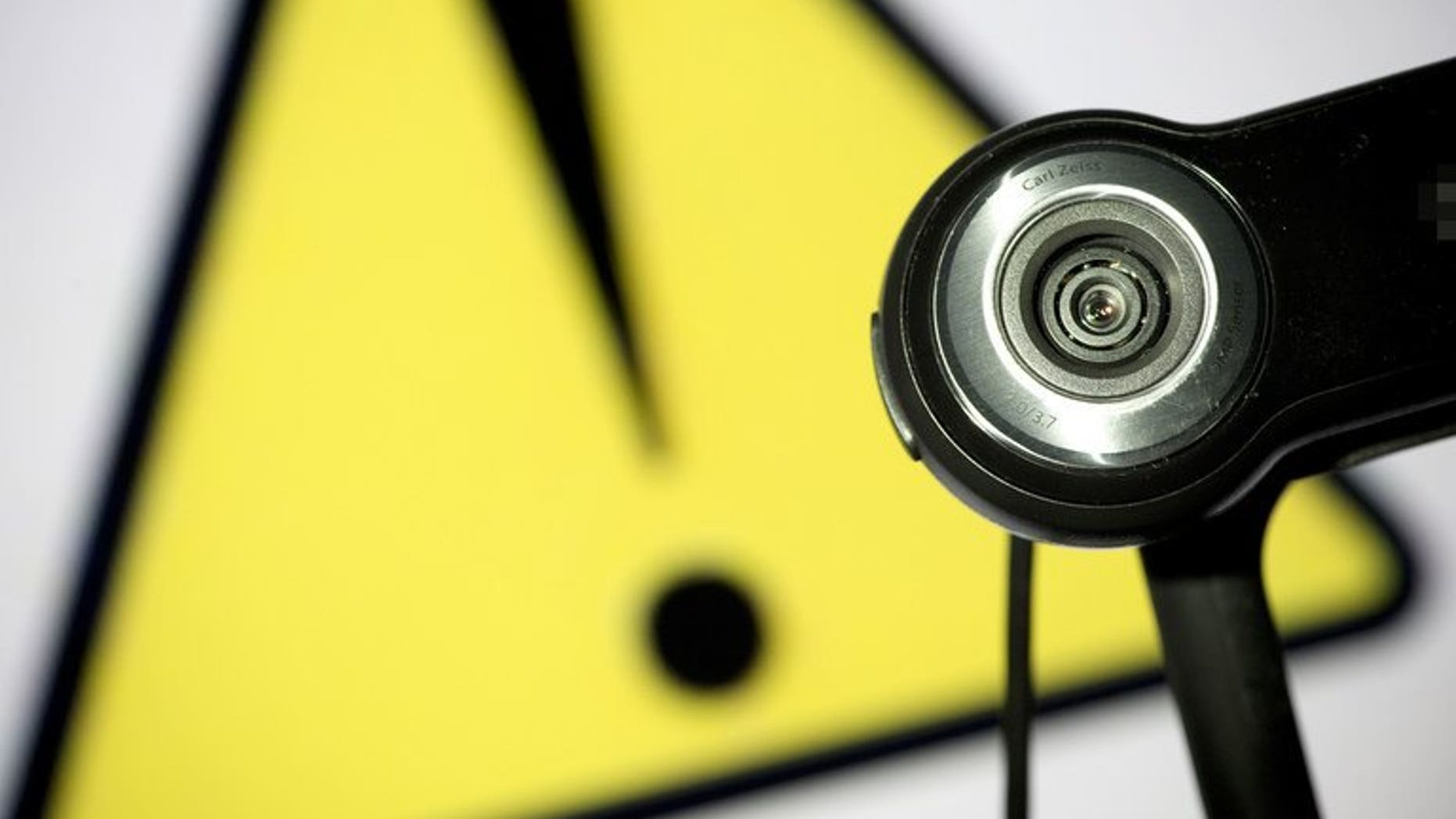 This file illustration photo shows a webcam positioned in front of a danger sign. Two Canadian men were charged Friday in the distribution of child pornography linked to the suicide of a girl who killed herself after months of cyber-bullying, following a sexual assault.