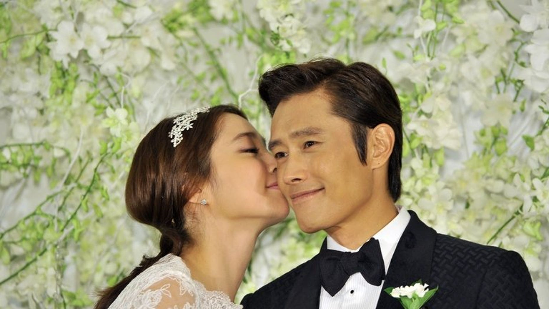"""South Korean actor Lee Byung-Hun poses with actress Lee Min-Jung during a press conference before their wedding in Seoul, on August 10, 2013. Lee Byung-Hun is one of the best known faces of the """"Korean Wave"""" of popular culture."""