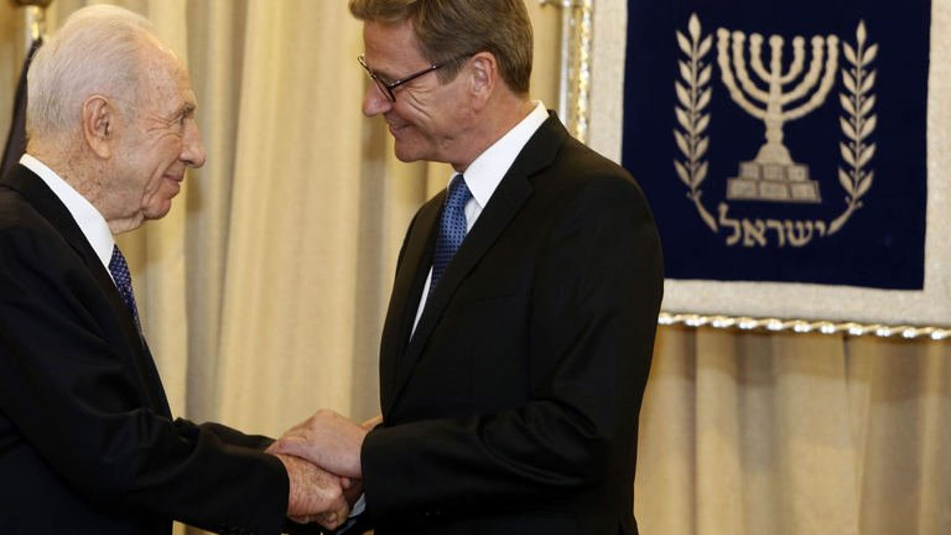 German Foreign Minister Guido Westerwelle (R) is greeted by Israeli President Shimon Peres (L) at the presidential residency in Jerusalem on August 11, 2013. Westerwelle met Sunday with Israeli officials on a visit to support nascent peace talks, offering to try to soften a European ban on dealings with Jewish settlements.