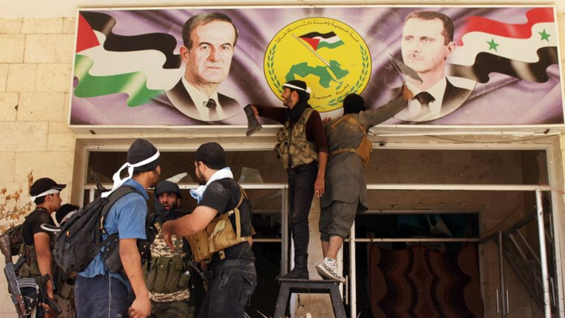 Rebel fighters tear down a poster of Syrian President Bashar al-Assad (R) and his late father and predecessor Hafez al-Assad (L) in the town of Deir Ezzor, on August 10, 2013. Nearly 60 Syrian soldiers and jihadists have been killed in three days of fighting in Deir Ezzor, the largest city in eastern Syria, where rebels have made advances, an NGO said Monday.