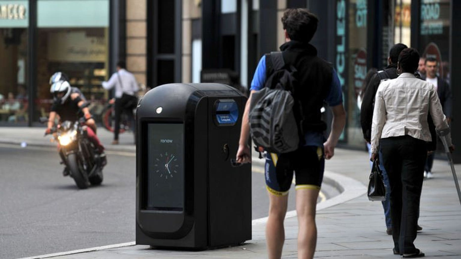"""People walk past a """"pod"""" high-tech trash bin in the City of London on August 12, 2013. Authorities in London's financial district ordered Renew, a company using high-tech trash cans to collect smartphone data from passers-by, to cease its activities, and referred the firm to the privacy watchdog."""