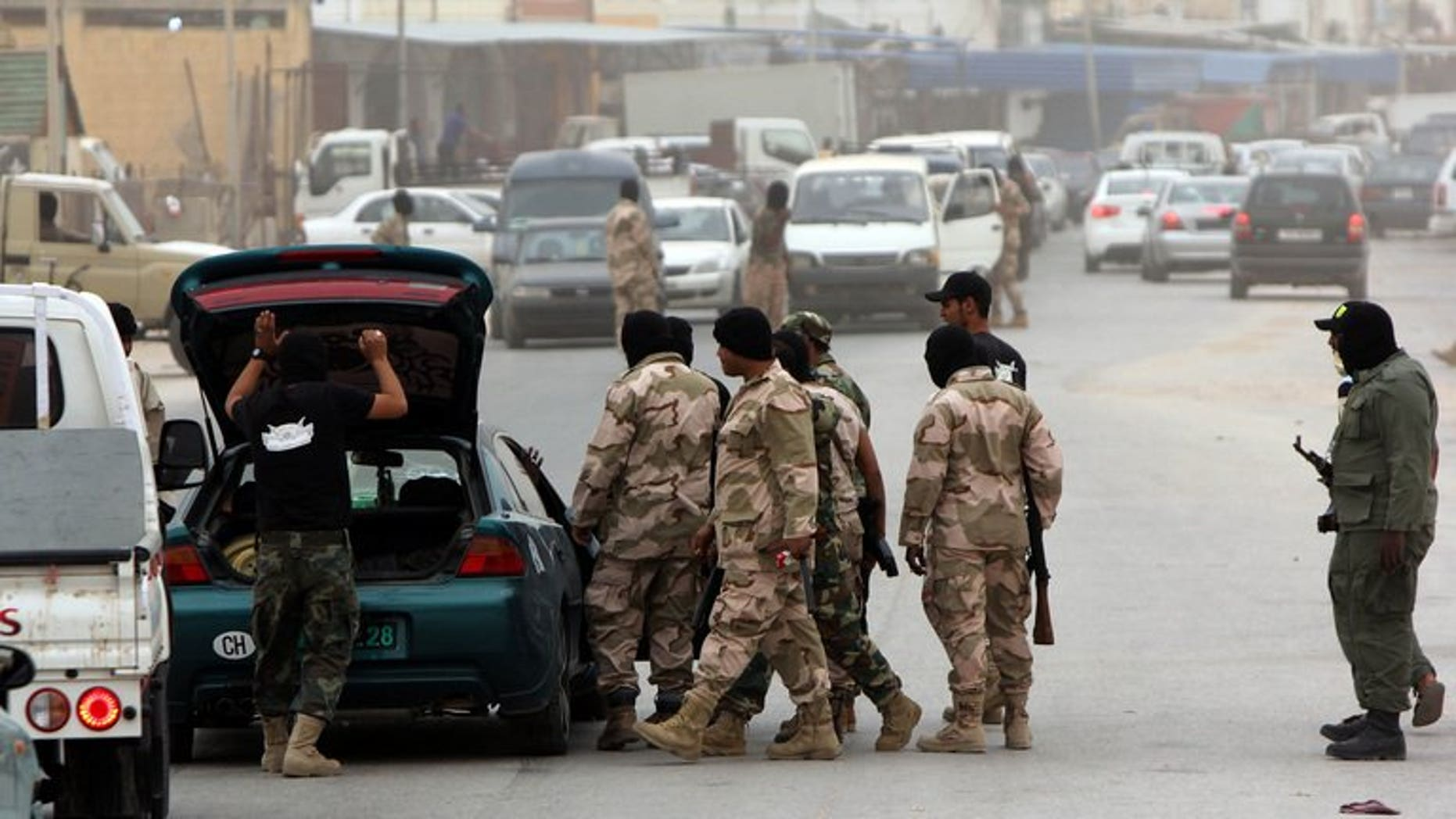 Libyan security force officers search a car at a checkpoint on May 16, 2013 in Benghazi. Some 14,000 prisoners who escaped from various Libyan detention centres after the 2011 uprising against Moamer Kadhafi are still on the run, the interior minister said.