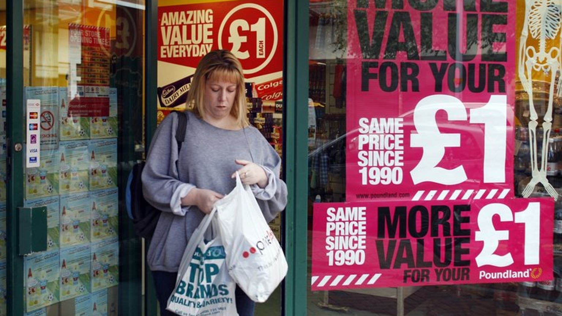 A woman leaves a shop in Reading on October 1, 2008. Britain's annual inflation fell in July from a 14-month peak reached in June, official data showed.