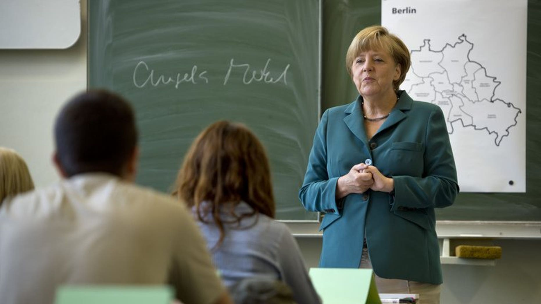 German Chancellor Angela Merkel talks to students during her visit to the Heinrich Schliemann secondary school in Berlin, on August 13, 2013. Merkel, campaigning for a third term, filled in as a school history teacher on the 52nd anniversary of the building of the Berlin Wall.