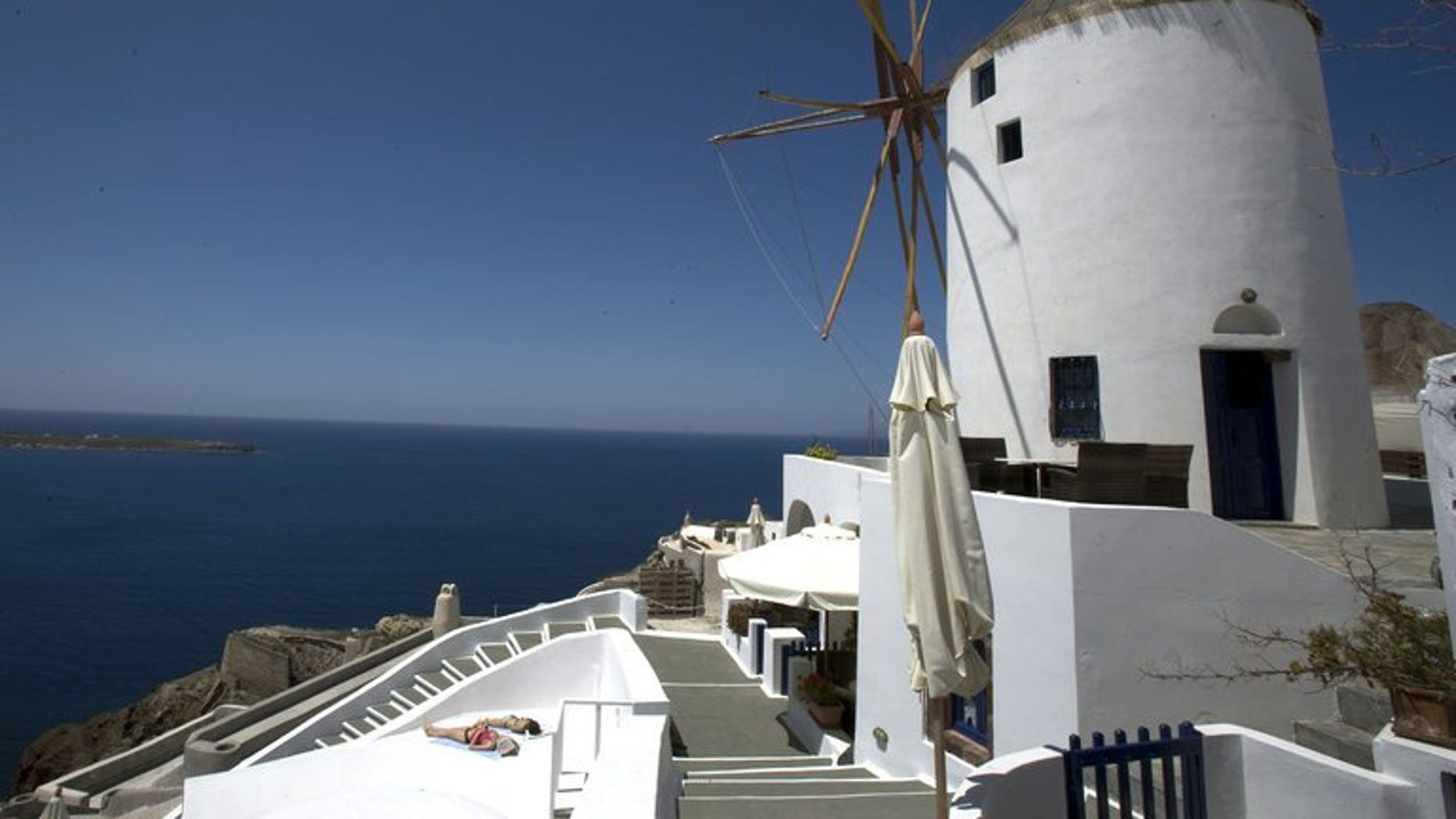 A photo taken on April 24, 2008 shows tourists sunbathing on the Greek island of Santorini. The Greek island of Santorini -- one of the country's premier travel destinations -- has been hit with a sweeping power shortage after a fire at the island's main electricity plant.