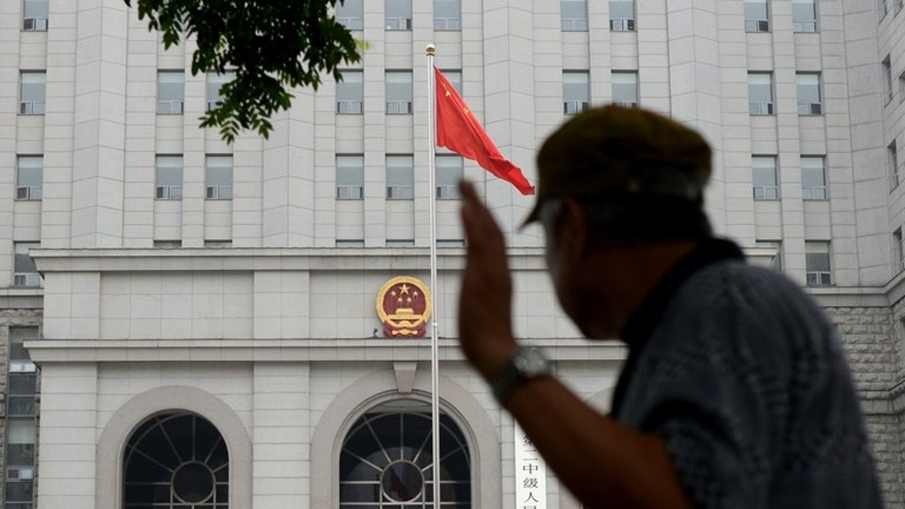 A Chinese civilian walks past a courthouse in Beijing, on July 8, 2013. China for the first time has issued guidelines aimed at preventing wrongful or unjust court judgements in response to high-profile judicial scandals, state media reported.