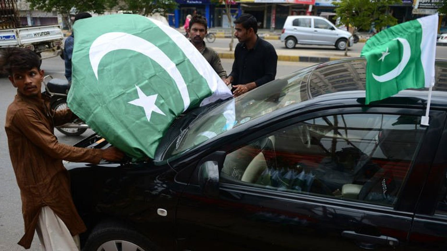 Pakistani vendors decorate a car with national flags ahead of the country's Independence Day in Karachi on August 12, 2013. Twin hand grenade attacks killed at least two people and wounded 28 others belonging to a Shiite Muslim community in Pakistan's port city of Karachi on Tuesday, officials said.