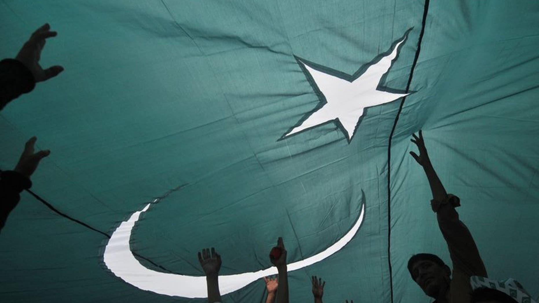 Youths gather under a giant national flag in Lahore on August 13, 2013, one day ahead of the country's Independence Day. At least one person was killed and more than 30 wounded in Karachi on Wednesday as hundreds of people fired guns in the air to celebrate Pakistan's Independence Day.