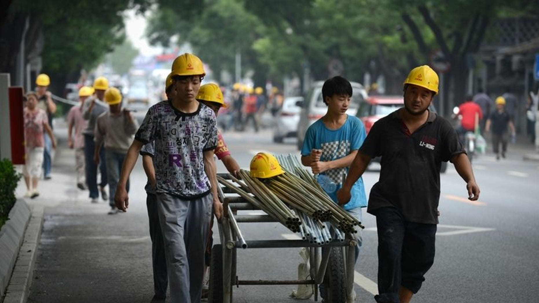 Chinese workers pull steel tubes near a construction site in Beijing on July 11, 2013. Tracking the flows of China's 263 million migrant workers is a huge challenge, but officials have found the answer in packs of pickled root vegetables.