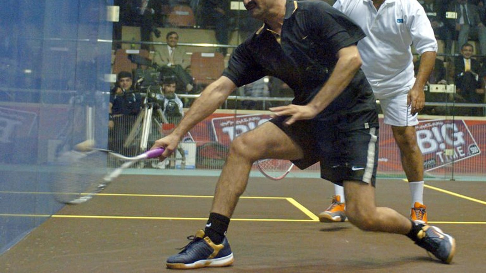 """Pakistani squash legends Jahangir Khan (right) and Jansher Khan play during a friendly match at the Mushaf Squash Complex in Islamabad, 14 December 2005. Khan says the country must do more to improve its image and stop the rest of the world thinking of Pakistanis as """"terrorists""""."""