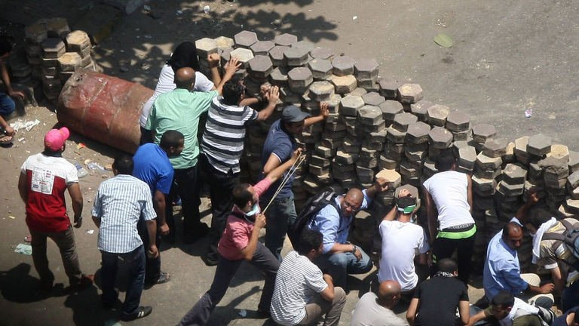 Egyptian supporters of ousted president Mohamed Morsi confront riot police at Mustafa Mahmoud Square in Cairo, on August 14, 2013. Egypt's government has declared a curfew in Cairo and 10 other provinces in a bid to contain nationwide violence following a crackdown on Morsi's supporters.