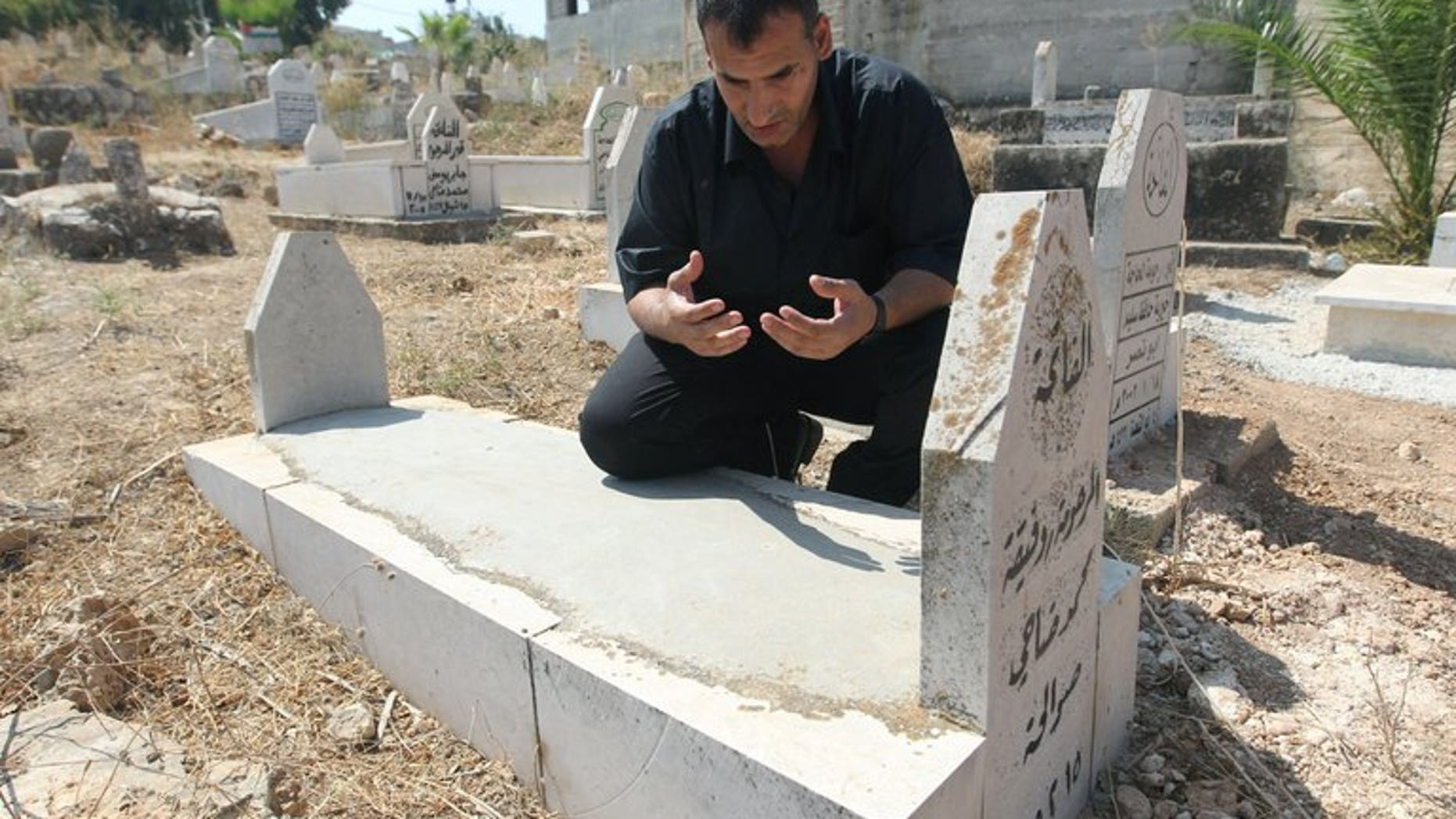 Released Palestinian prisoner Hosni Sawalha prays at the graves of his parents -- who died while he was in an Israeli jail -- in the the West Bank village of Azmut, on August 14, 2013. Tears streamed down Sawalha's face as he recited from the Koran alongside the graves of his parents, who died while he was in Israeli jail since his teens.