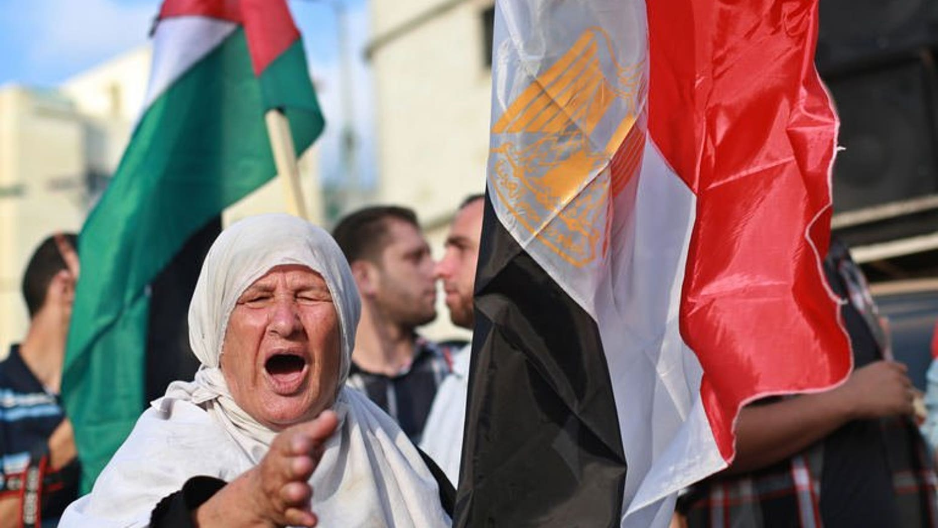 """A Palestinian supporter of ousted Egyptian president Mohamed Morsi, shouts slogans as she stands in between the Egyptian (R) and Palestinian flags during a protest against the violence in the Egyptian capital on August 14, 2013, in Gaza City. The Palestinian Islamist movement Hamas condemned Egypt's bloody crackdown on supporters of ousted president Mohammed Morsi as a """"terrible massacre."""""""