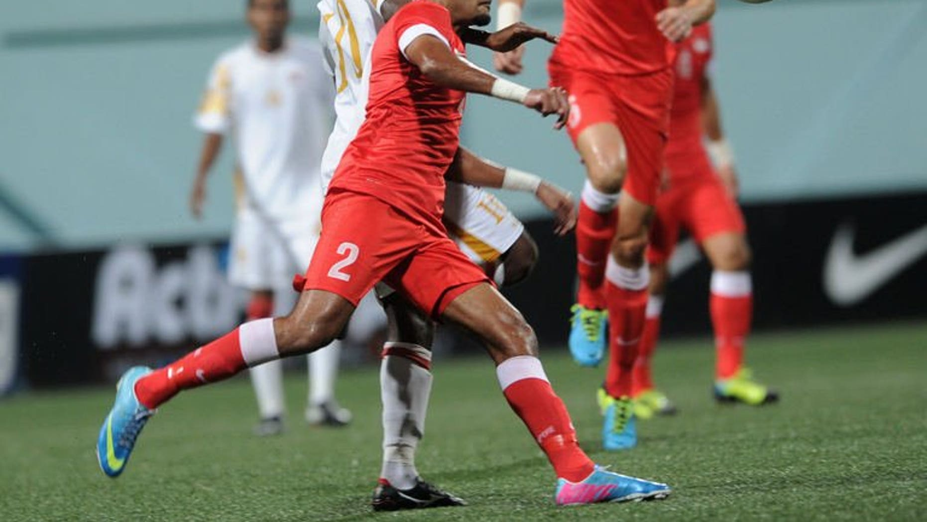 Oman midfielder Qasim Said (R) and Singapore defender Muhammed Faritz (L) fight for the ball during the AFC Cup Australia 2015 qualifiers in Singapore on August 14, 2013. Oman won 2-0.