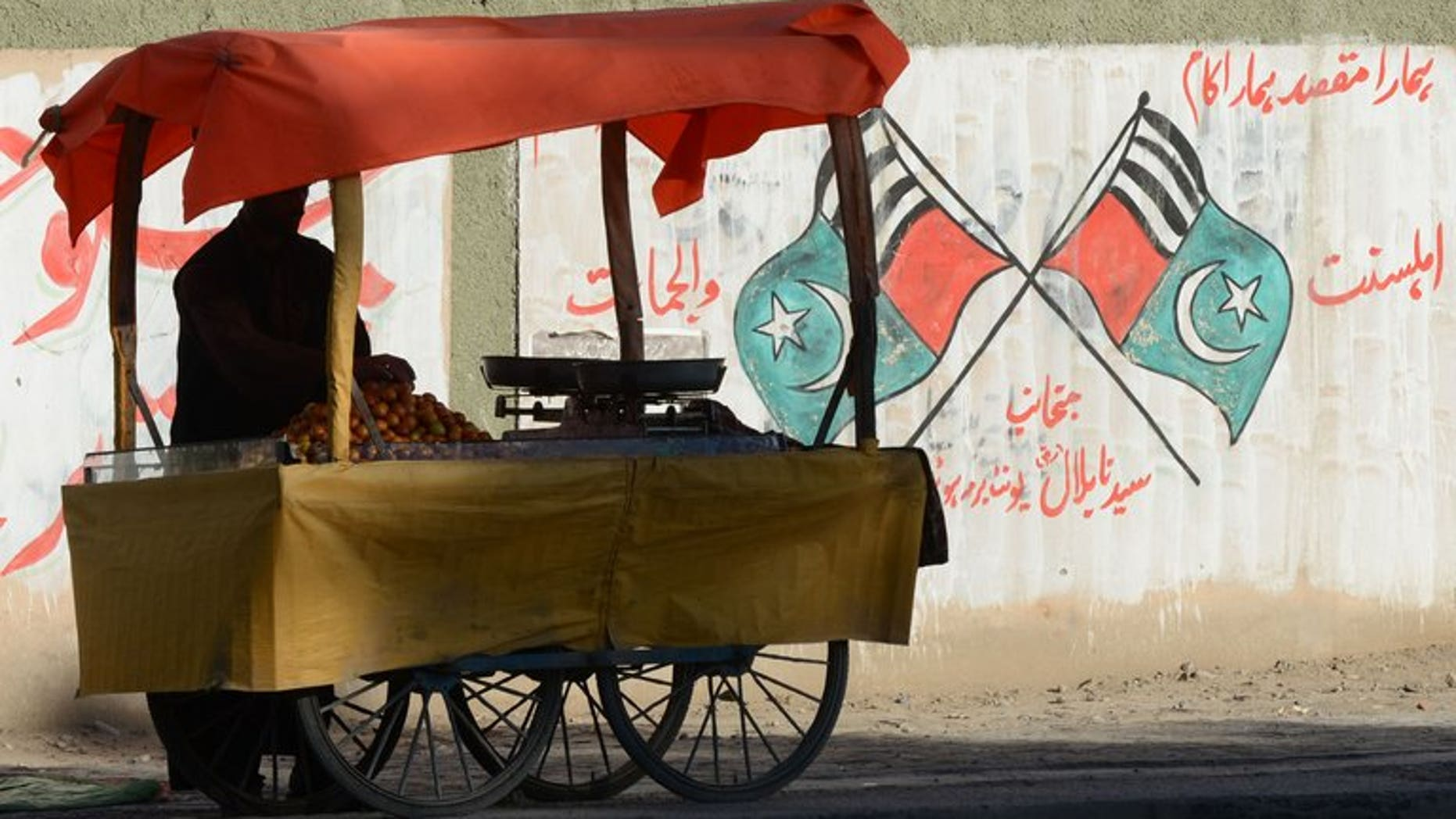 """A Pakistani vendor waits for customers near grattifi messages and scrawled flags of Jihad and Ahle Sunnat Wal Jamaat, the """"political wing"""" of a banned militant faction Lashkar-e-Jhangvi in Quetta on March 5, 2013. Pakistan will hang two convicted militants next week, officials said, despite a Taliban warning that it would regard the execution of any of its members as a """"declaration of war""""."""