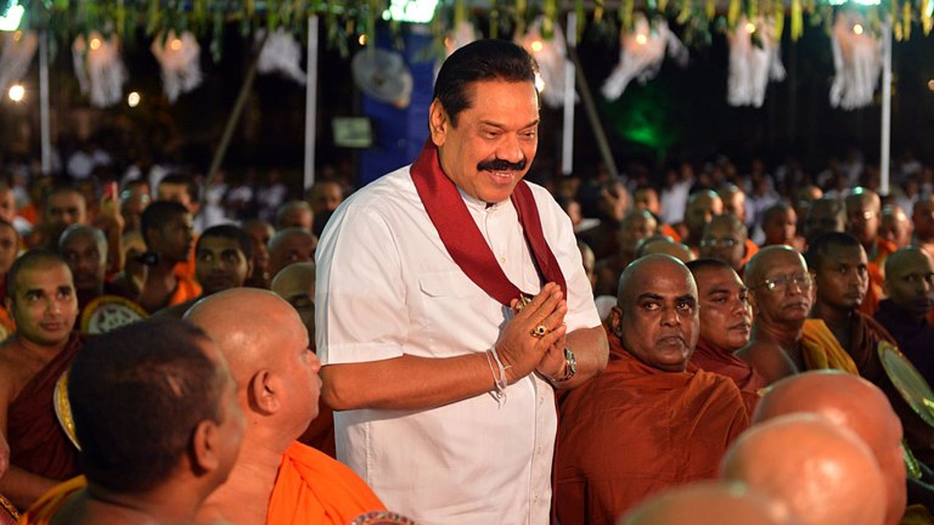 Sri Lankan President Mahinda Rajapakse (C) walks past Buddhist monks during the War Heroes religious ceremony in Colombo on May 9, 2013. Rajapakse ordered a new investigation into the disappearance of thousands of people in the island's northeast during an ethnic war which ended four years ago.