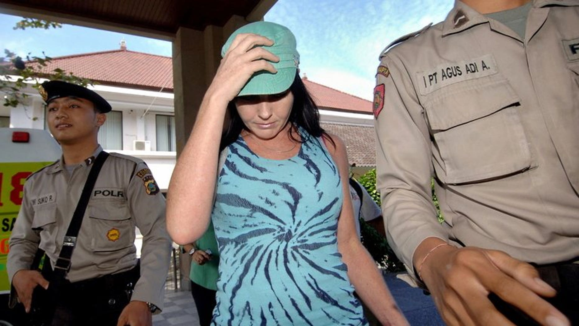 Convicted Australian drug trafficker Schapelle Corby (C) is escorted by two policemen in Denpasar on Bali island on July 2, 2008. Corby is one step closer to being freed from prison in Indonesia's Bali island after officials began preparing for her parole, her sister said Wednesday.