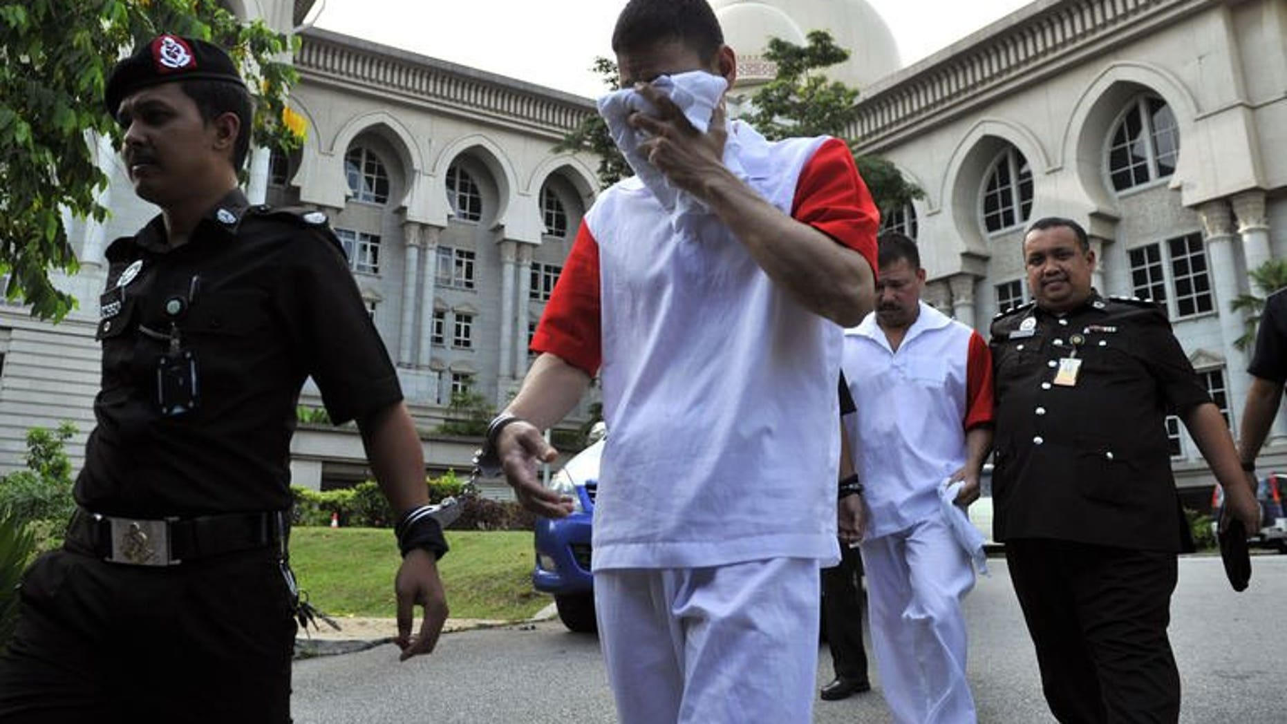 Malaysian prison personnel escort Mexican brothers Jose Regino Gonzalez Villarreal (2nd L) and Luis Alfonso Gonzalez Villarreal (2nd, R) as they leave the appeals court in Putrajaya on August 14, 2013. Malaysia's appeals court upheld the decision to hang three Mexican brothers to death for drug trafficking, forcing them to head to the nation's apex court as a last resort.