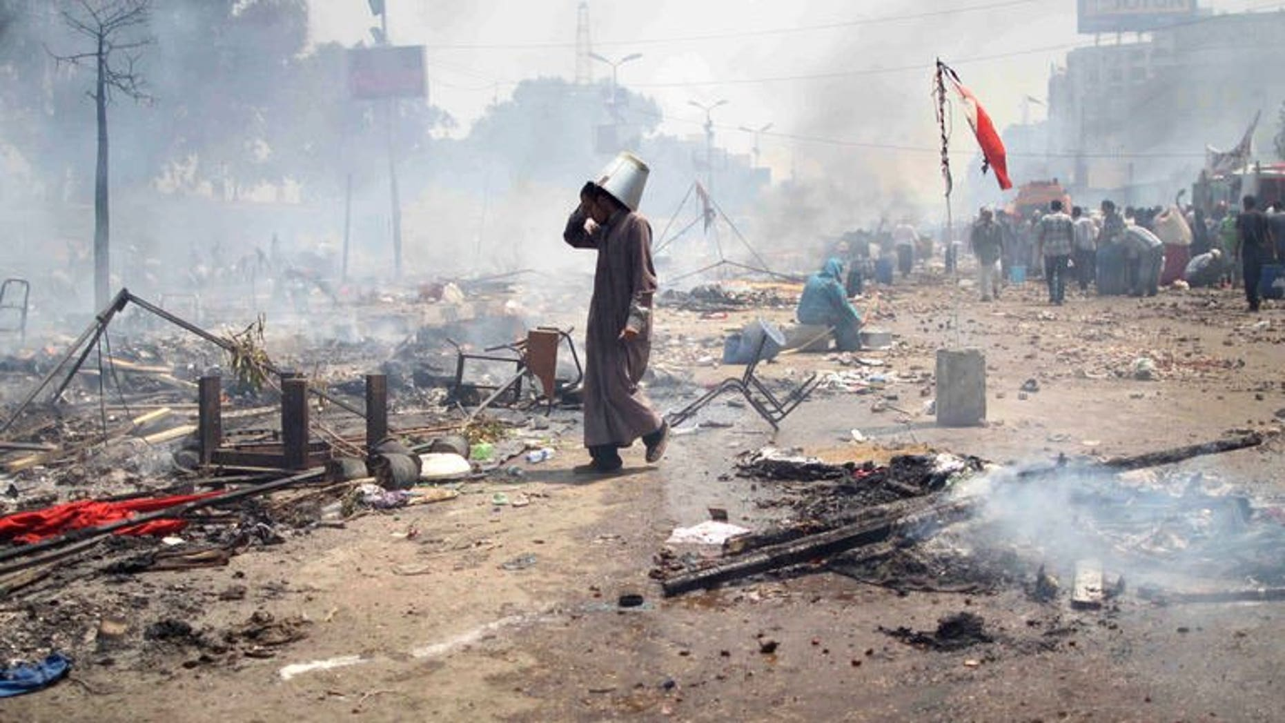 """A supporter of Egypt's ousted president Mohamed Morsi walks through the debris following clashes with police in Cairo on August 14, 2013. Egyptian security forces were in """"total control"""" of the main protest camp of supporters of ousted president Mohamed Morsi on Wednesday after a day of deadly clashes, a security official said."""