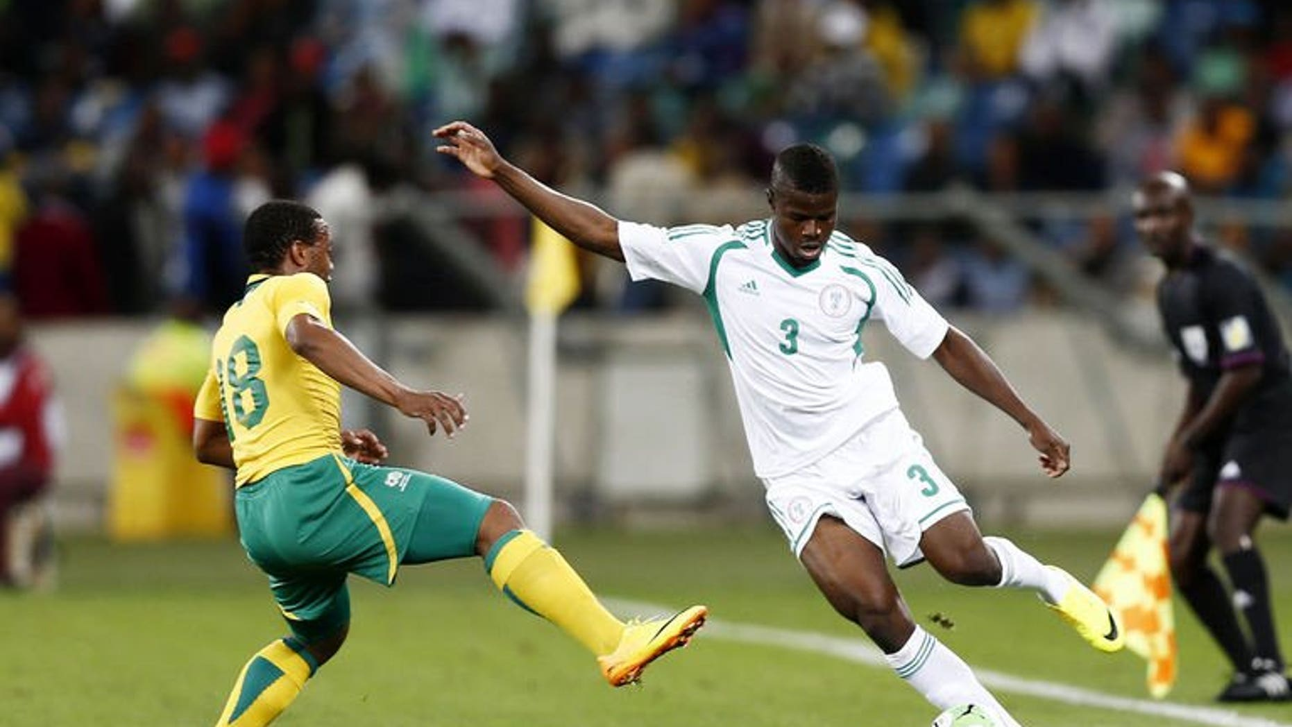 Nigeria's Elderson Echiejile (R) passes the ball away from South Africa's Thuso Phala during the 2013 Nelson Mandela football Challenge friendly match between South Africa and Nigeria at Moses Mabhida Stadium on August 14, 2013 in Durban, South Africa. Nigeria won 2-0.