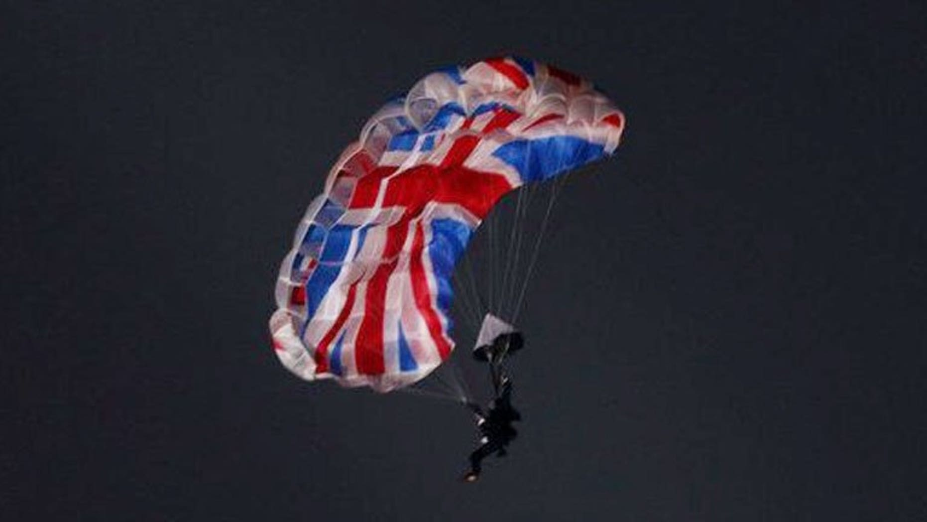 Mark Sutton, a stuntman playing the role of Daniel Craig as James Bond, parachutes out of a helicopter during the London Olympics opening ceremony on July 27, 2012. Sutton has died while wing-diving in Switzerland, British press reported Thursday.