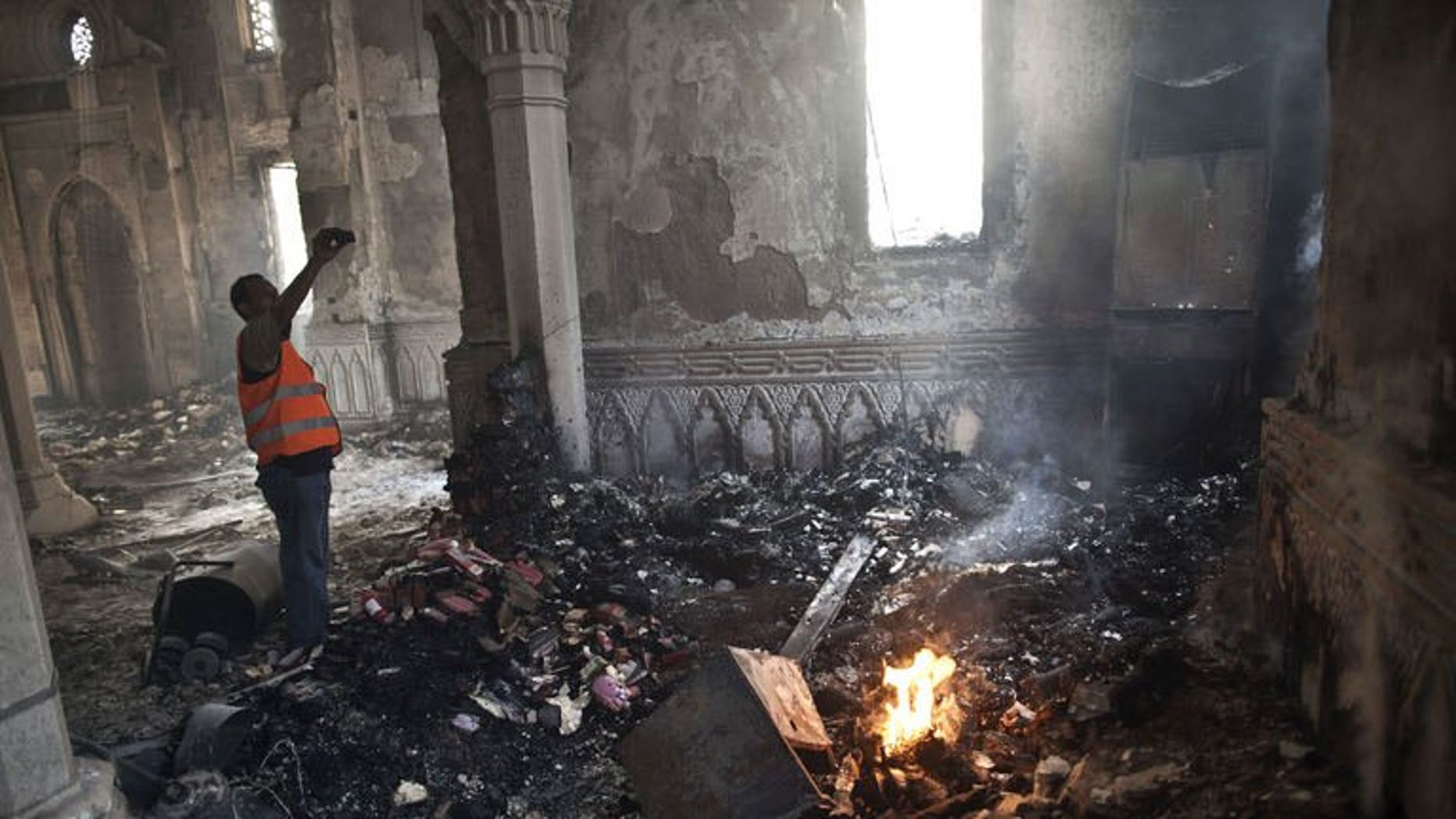 """An Egyptian stands near a burning fire as he takes a picture of the damage at Rabaa al-Adawiya mosque in Cairo, on August 15, 2013. French President Francois Hollande says """"everything must be done to avoid a civil war"""" in Egypt, after a crackdown by security forces on supporters of ousted Islamist president Mohamed Morsi left over 460 people dead."""