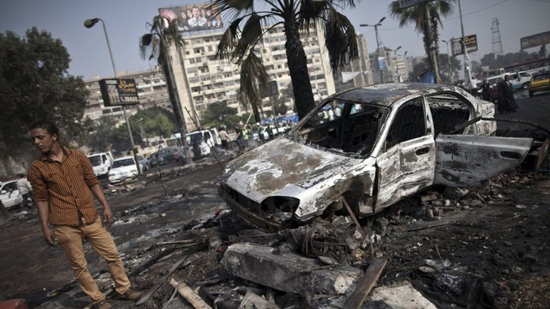 """A man stands amidst the debris at Rabaa al-Adawiya square in Cairo on Thursday. Britain has summoned Egypt's ambassador to express its """"deep concern"""" at the violence in the country and urged the authorities to act with """"the greatest restraint"""", the Foreign Office said on Thursday."""