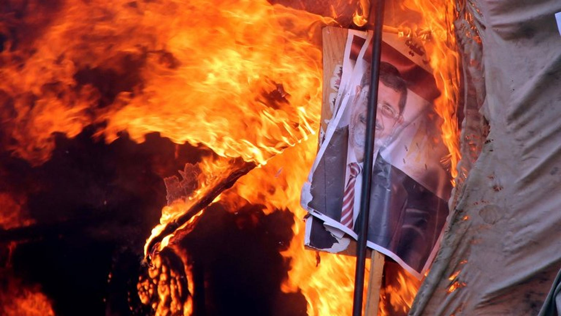 A protest camp is set ablaze after Egyptian police dispersed supporters of ousted president Mohamed Morsi (portrait) from the al-Nahda Square in Cairo, on August 14, 2013. Egyptian Islamist protesters have stormed the Giza governorate headquarters in Cairo, and set it on fire, according to state television.