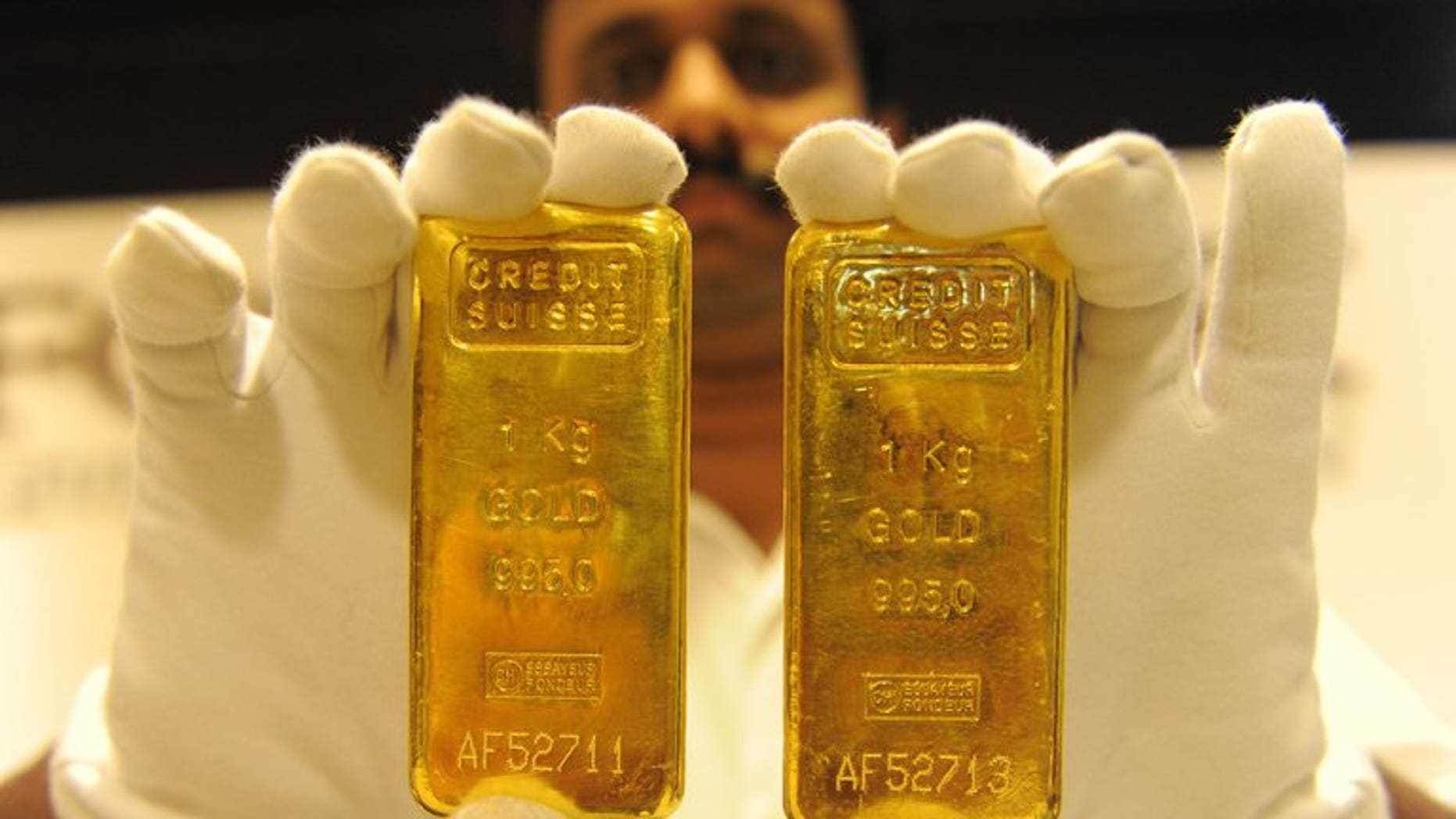 A jewellery shop employee displays 24-carat gold bars in Ahmedabad on August 20, 2011. Global demand for gold fell to a four-year-low in the second quarter despite a surge in demand from India and China as the metal became cheaper, the World Gold Council said Thursday.