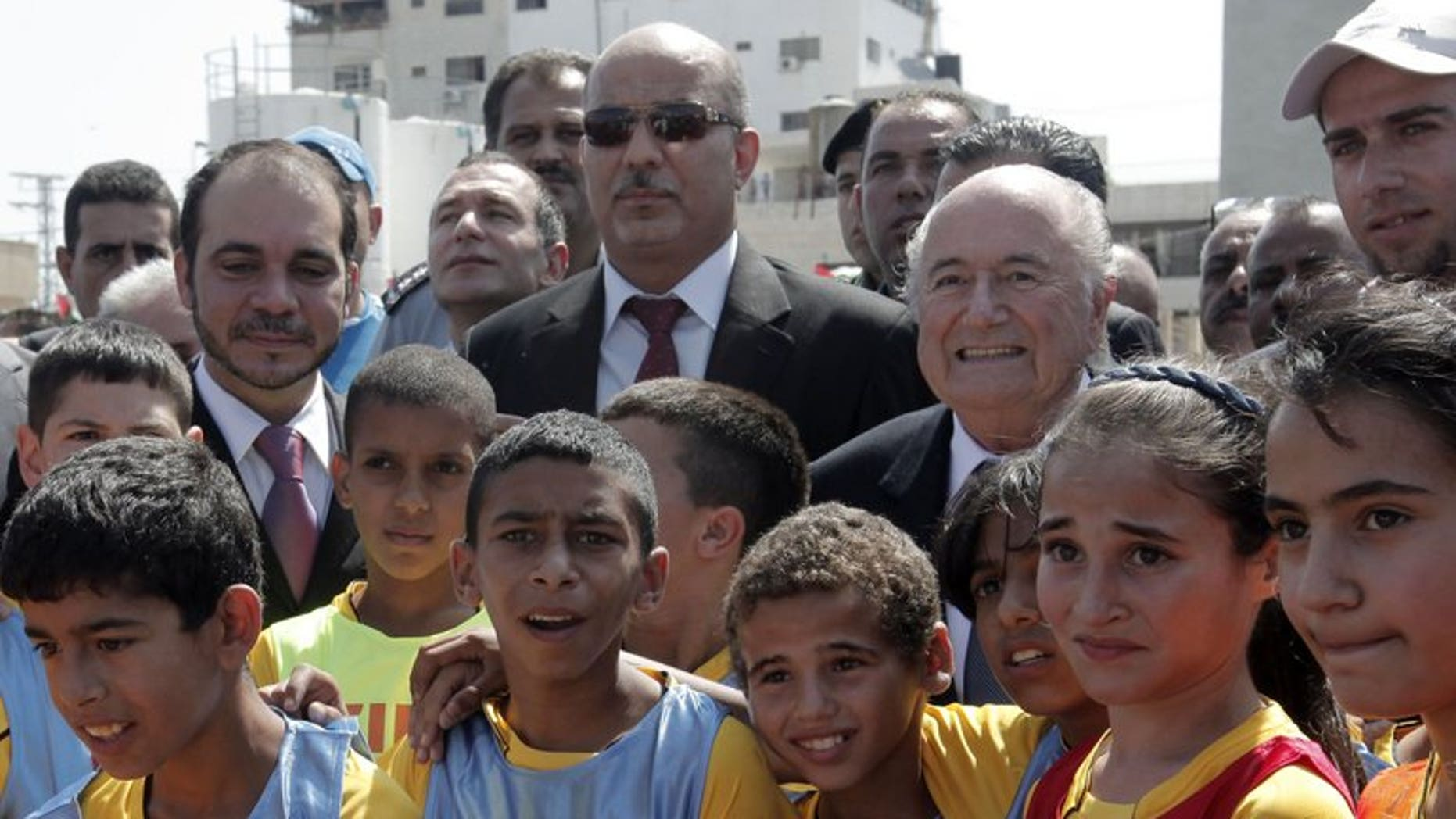 FIFA President Sepp Blatter (centre right), Palestinian Football Association chairman Jibril Rajoub (centre) and FIFA Vice-President Prince Ali bin al-Hussein with Palestinian children in the West Bank town of Tulkarm July 7, 2013.