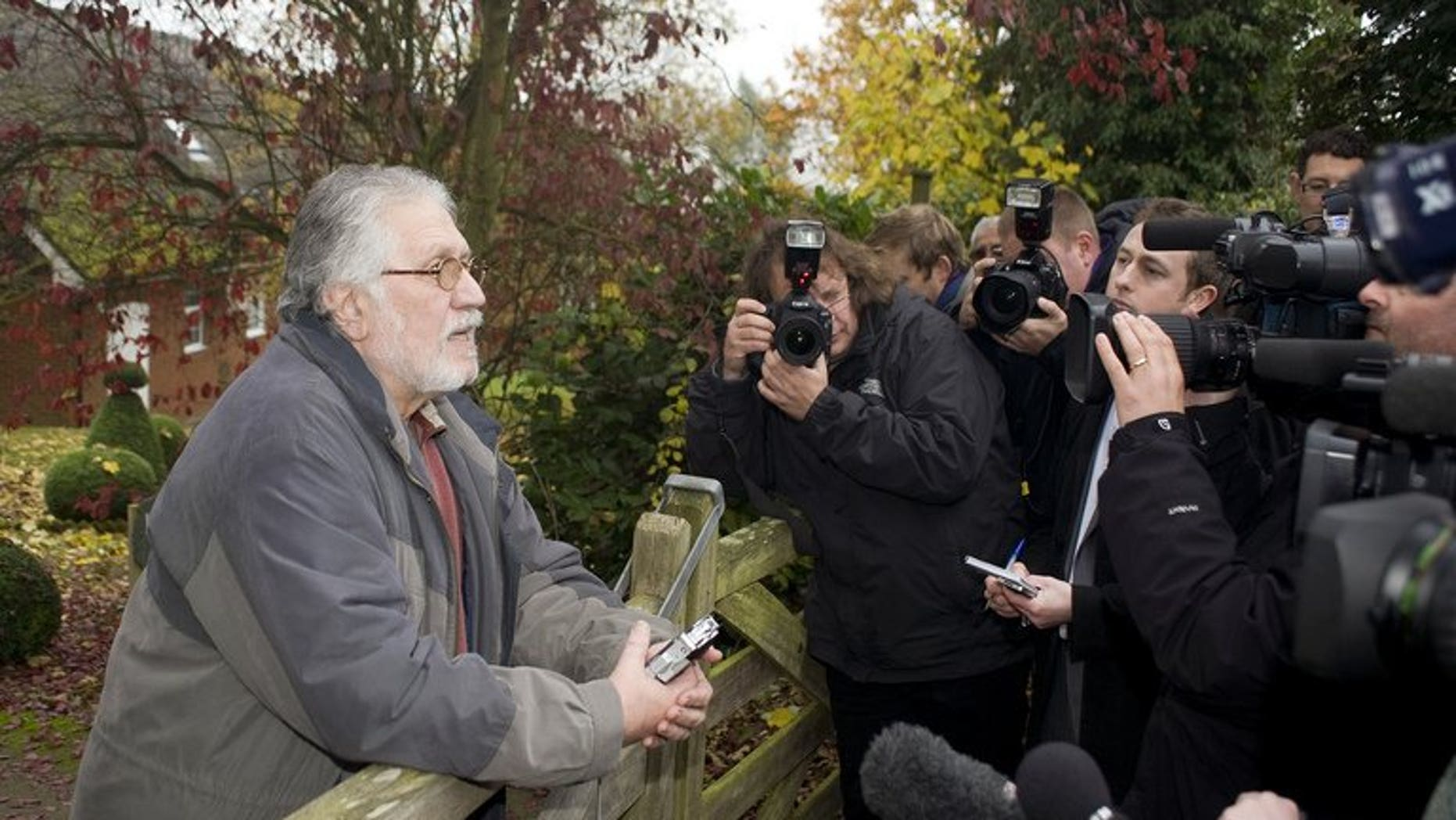 British radio and television presenter Dave Lee Travis (L) speaks to the media outside at his home in Buckinghamshire, England, on November 16, 2012. Travis was charged on Thursday with 11 counts of indecent assault of women and girls as young as 15 and one count of sexual assault, prosecutors said.