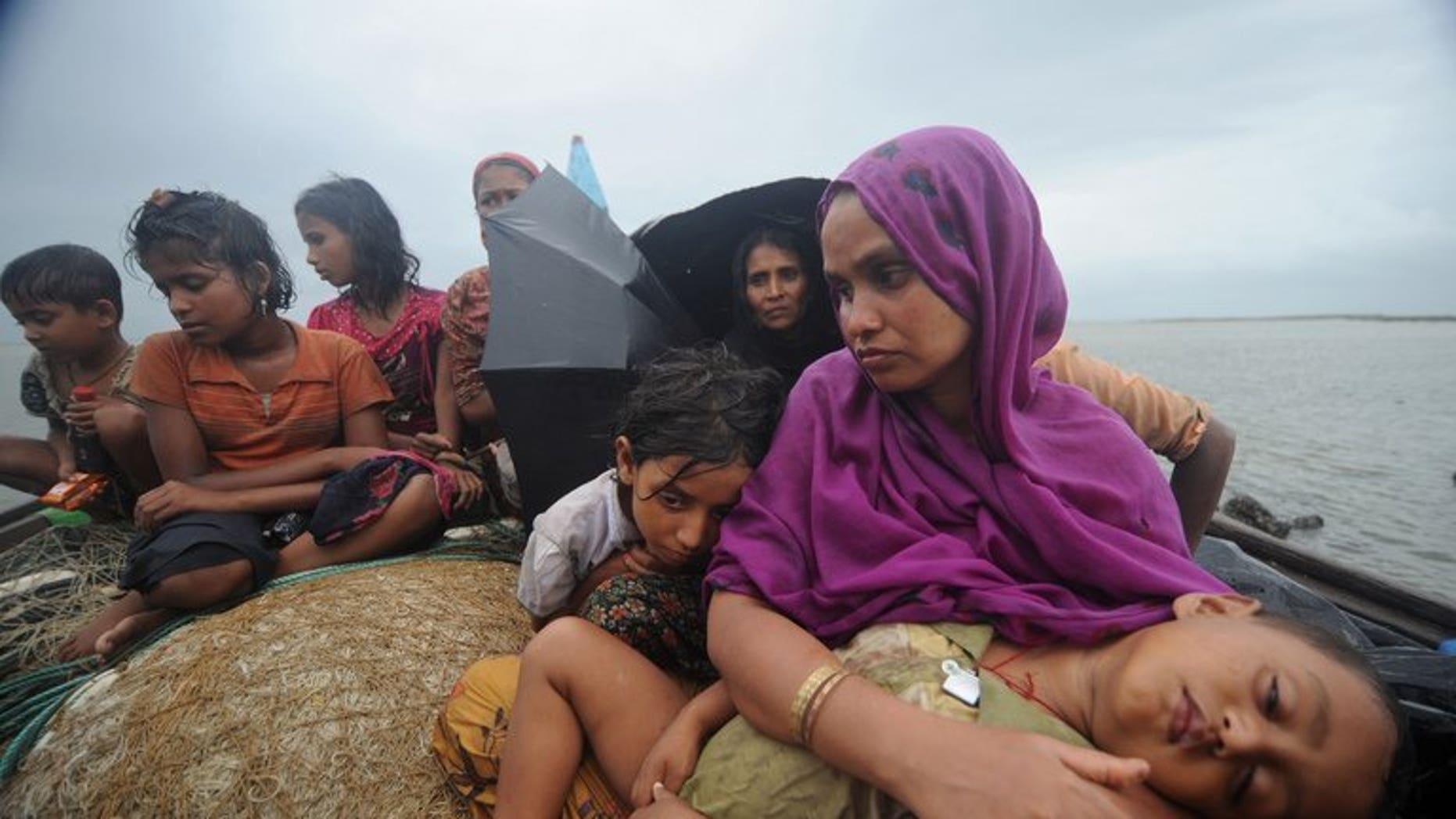 This picture taken on June 13, 2012 shows Rohingya Muslims, trying to cross the Naf river into Bangladesh to escape sectarian violence in Myanmar. Myanmar officials say six Buddhist men will face trial this month over the lynching of 10 Muslim bus passengers as sectarian unrest convulsed Rakhine state in June 2012.
