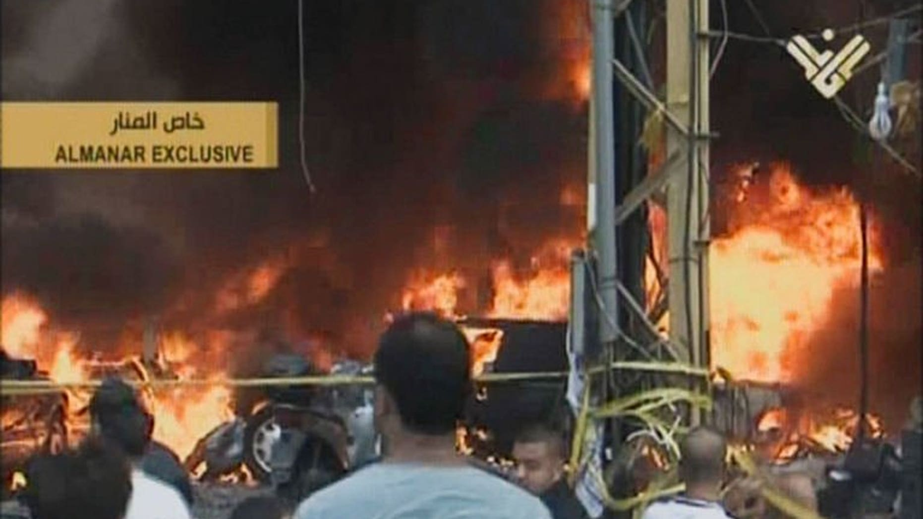 An image grab from Hezbollah's al-Manar TV shows Lebanese gathering at the scene of a car bomb in the majority Shiite southern suburb of Beirut on August 15, 2013.