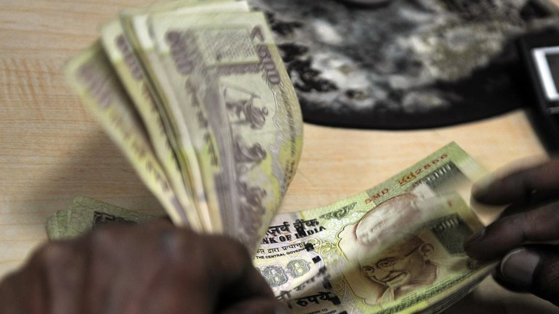 Indian rupee notes are being at a foreign exchange office in Mumbai, on August 6, 2013. The rupee plunged to a new record low against the dollar on Friday and stocks slid 2.66 percent over fears that foreign capital could flow back to the United States as the American economy improves.