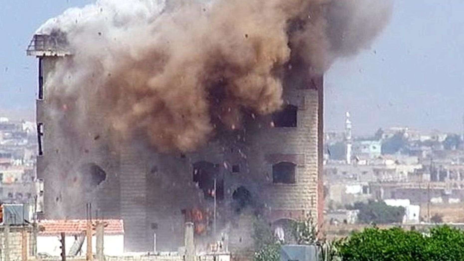 A picture released on June 2 shows smokes rising as a mortar shell hits a building in al-Hula in Homs province. Mortar fire by the Syrian army on the Mleha district southeast of Damascus killed at least 14 civilians, four of them children, a watchdog said on Friday.