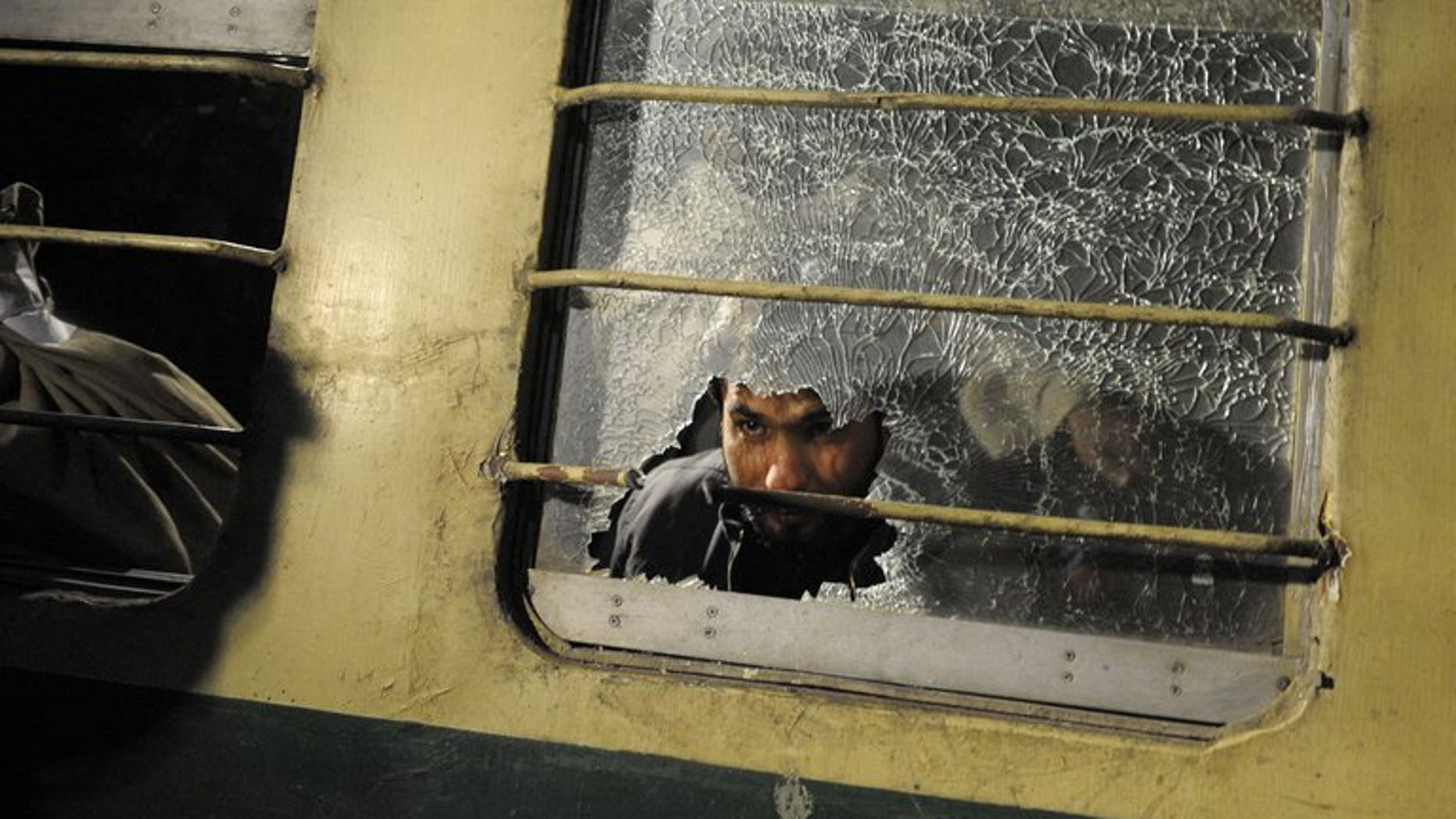 A man looks through a broken mirror on a train after an attack at a railway station in Quetta last year. Unidentified militants killed two people and wounded 24 Friday in a gun and rocket attack on a passenger train in restive southwest Pakistan, officials said.