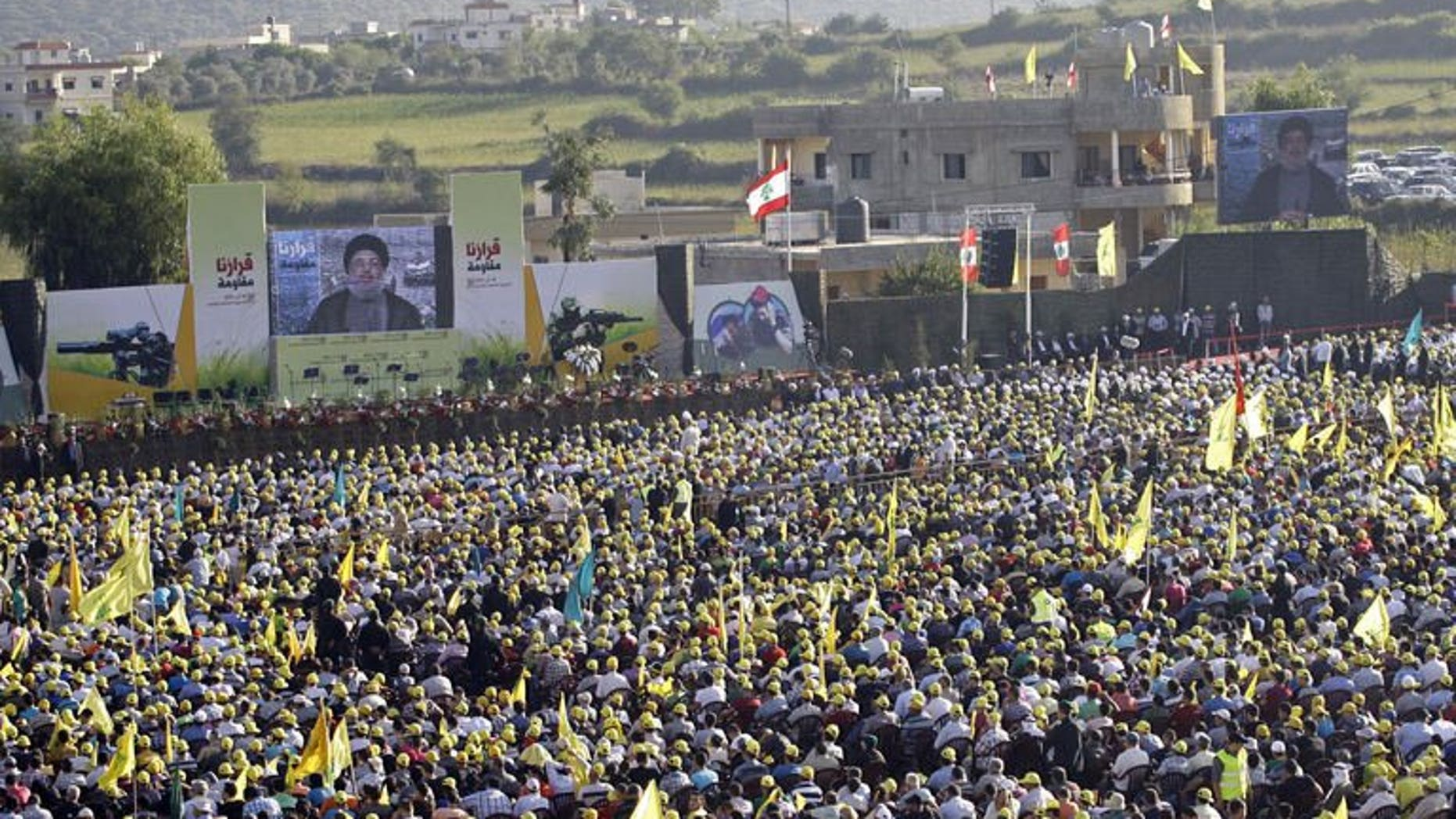 Lebanese supporters of the Shiite Hezbollah movement listen to Hezbollah's leader Hasan Nasrallah delivering a televised speech as they gather in the southern Lebanese village of Aita al-Shaab, on the border with Israel on August 16, 2013 to commemorate the seventh anniversary of the 2006 July-August war between Lebanon and Israel.