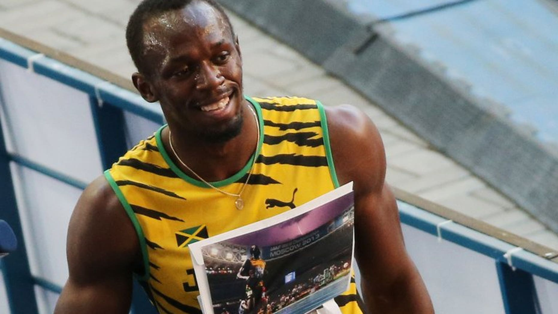 Jamaica's Usain Bolt poses with an AFP picture by photographer Olivier Morin after the men's 200 metres semi-final at the 2013 IAAF World Championships at the Luzhniki stadium in Moscow on August 16, 2013.