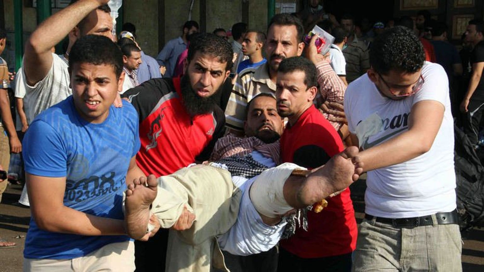 Egyptian Muslim Brotherhood supporters carry a wounded comrade near Ramses square in Cairo on August 16, 2013. France and Britain called Friday for Europe to send a strong message on the escalating crisis in Egypt, urging the EU to review its relations with Cairo.