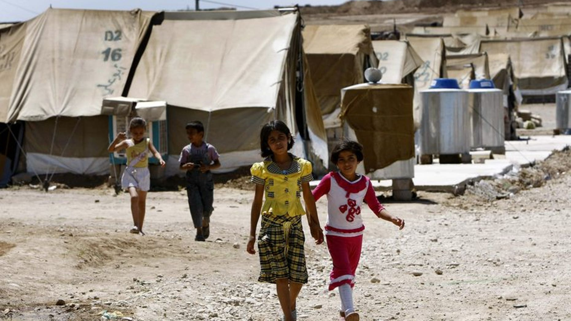 Syrian-Kurdish children walk on June 8, 2012 in the Domiz refugee camp, 20 km south-east of Dohuk city. The UN refugee agency said Friday it was scrambling aid in northern Iraq after thousands of Syrians crossed the tightly-controlled border in a sudden and unexplained influx.
