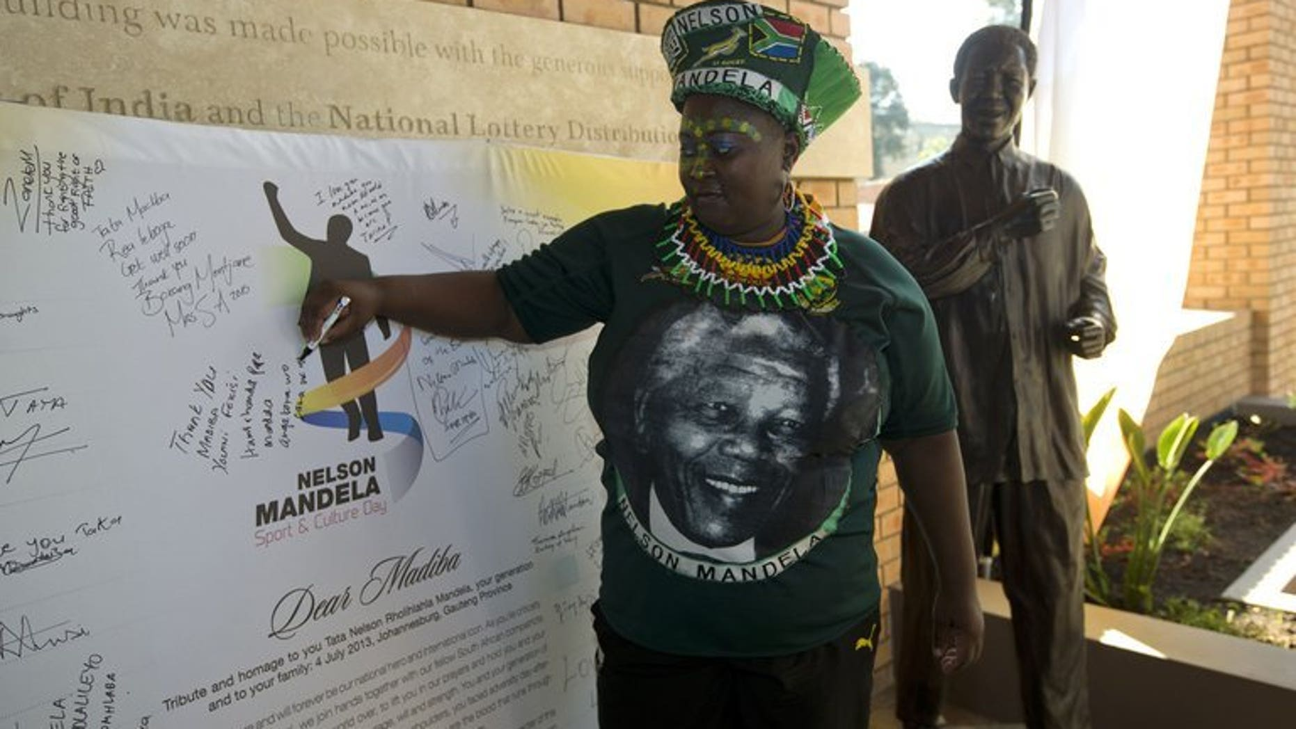 A rugby fan writes a message to Nelson Mandela in Johannesburg on July 4, 2013. South Africa's national team will have an outline image of Nelson Mandela on a sleeve of their shirts when they tackle Argentina Saturday in the Rugby Championship.