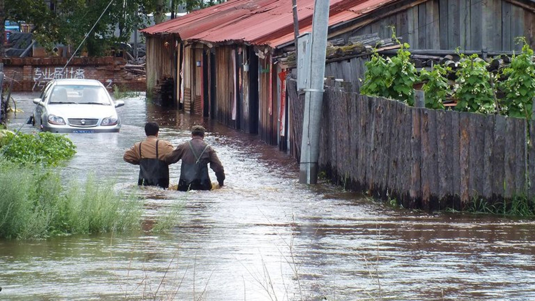 This picture taken on July 25, 2013 shows local residents wading in a flooded area in Yakeshi, in northern China's Inner Mongolia region. Twenty-five people have been killed by floods which hit northeastern China over the past week, state media said Saturday, as other parts of the country continued to experience a heatwave.