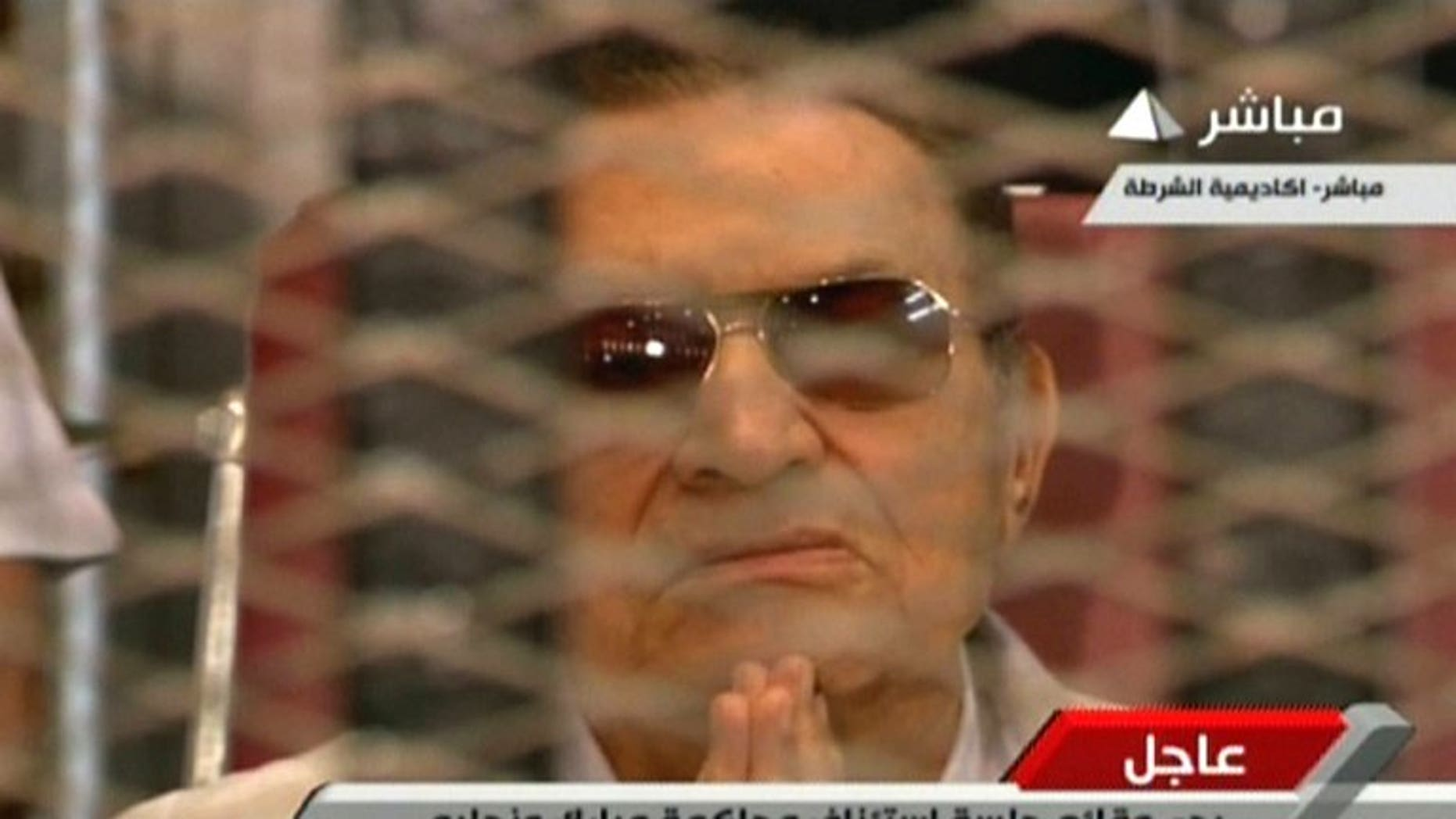 An image grab taken from Egyptian state TV shows ousted Egyptian president Hosni Mubarak gesturing behind bars during a hearing in his retrial at the police academy in Cairo on July 6, 2013. The trial of former Egyptian president Hosni Mubarak on charges of complicity in the deaths of protesters was adjourned on Saturday until August 25, after a brief session.