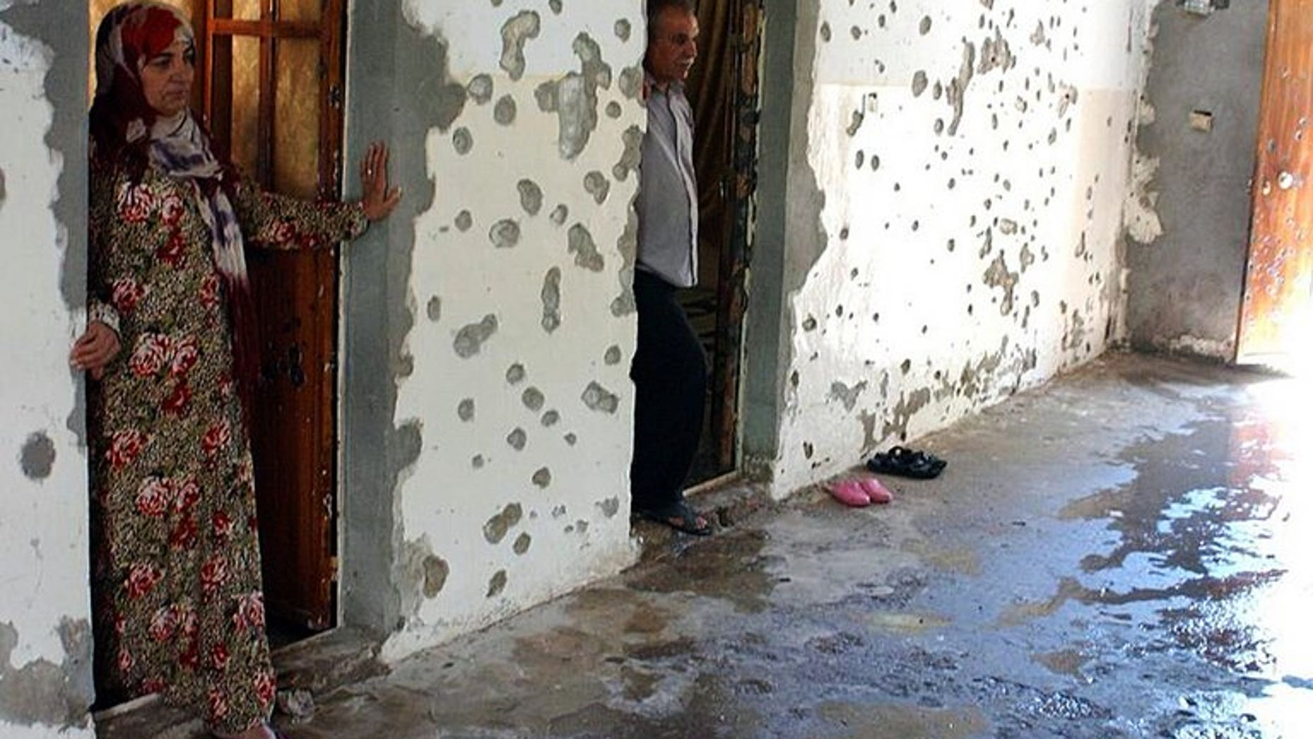A man and a woman stand next to a wall riddled with bullets in the courtyard of a house in the Syrian town of Ras al-Ain on August 3, 2013. Al-Qaeda loyalists attacked a mainly Kurdish town in northeastern Syria sparking fighting in which 17 people were killed, two of them ambulance crew, a watchdog said on Saturday.