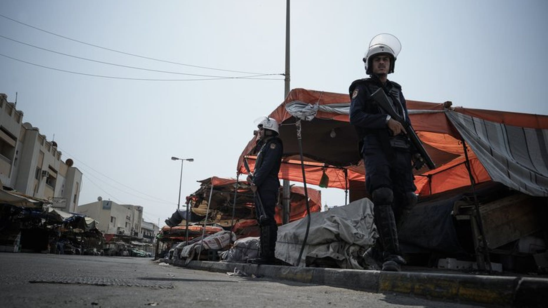 Bahraini police force officers on guard watching the road that runs through the market in the village of Jidd Hafs, west of Manama, on August 14, 2013. Bahrain's prosecutor has said it has launched a probe into riots at a detention centre as an activist said 40 prisoners were wounded as authorities restored order.